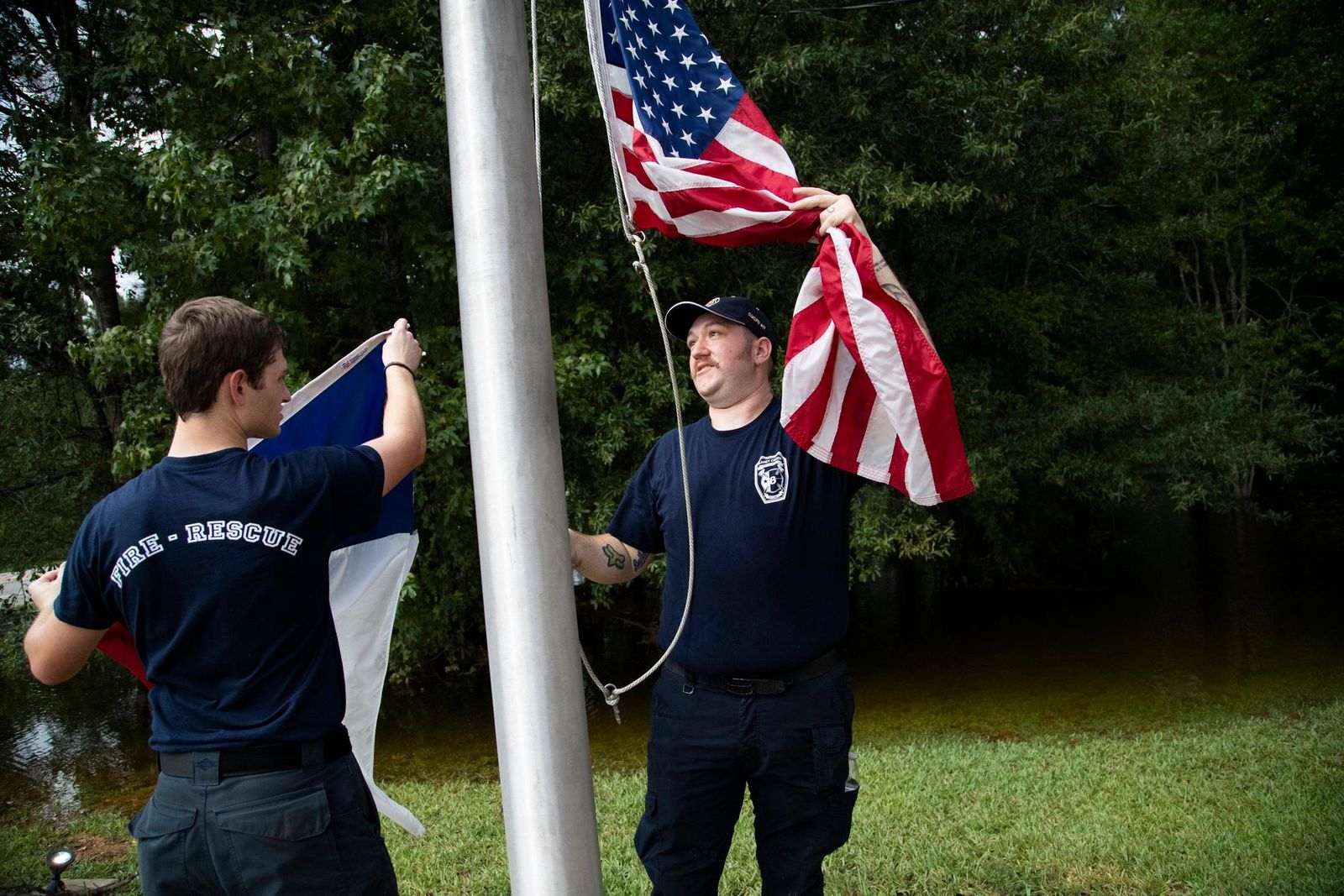Caney Creek Fire Department firefighters Avery Aultman, 21, left, Luke Hancock, 24, right, raise the United States flag and the Texan flag while cleaning up the fire station on Friday, Sept. 20, 2019, in Conroe, Texas, after it got flooded on Thursday. Floodwaters are starting to recede in most of the Houston area after the remnants of Tropical Storm Imelda flooded parts of Texas. (Marie D. De Jesus/Houston Chronicle via AP)