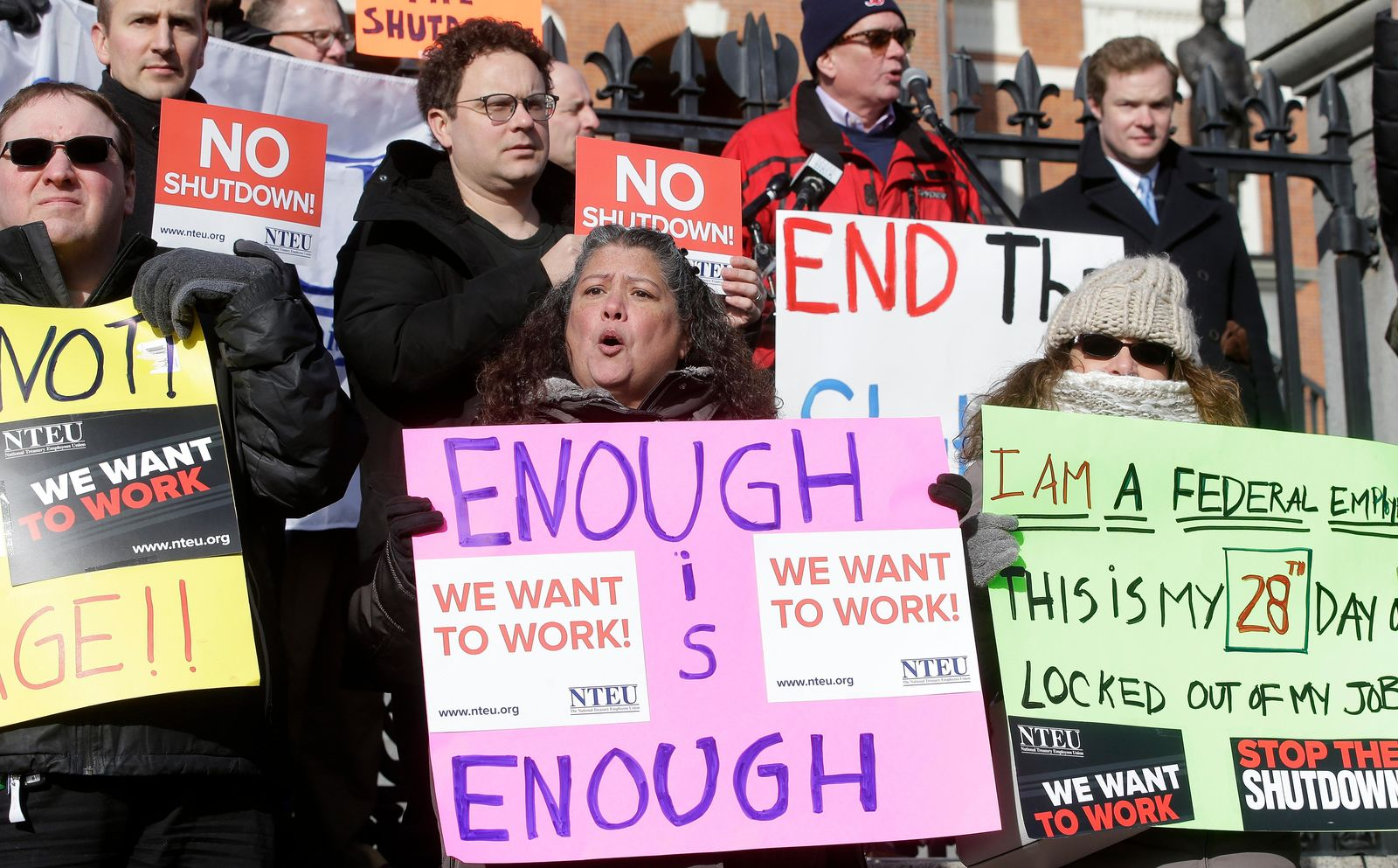 Internal Revenue Service employees, front row from the left, Brian Lanouette, of Merrimack, N.H., Mary Maldonado, of Dracut, Mass., and Maria Zangari, of Haverhill, Mass., display placards during a rally by federal employees and supporters, Thursday, Jan. 17, 2019, in front of the Statehouse, in Boston, held to call for an end of the partial shutdown of the federal government. (AP Photo/Steven Senne)