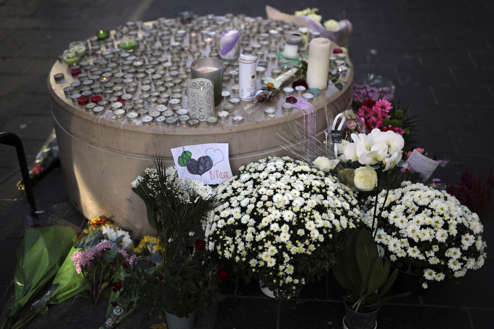 Flowers, messages and candles lie in front of the Notre Dame church, in Nice, France, Friday, Oct. 30, 2020.{ } (AP Photo/Daniel Cole)