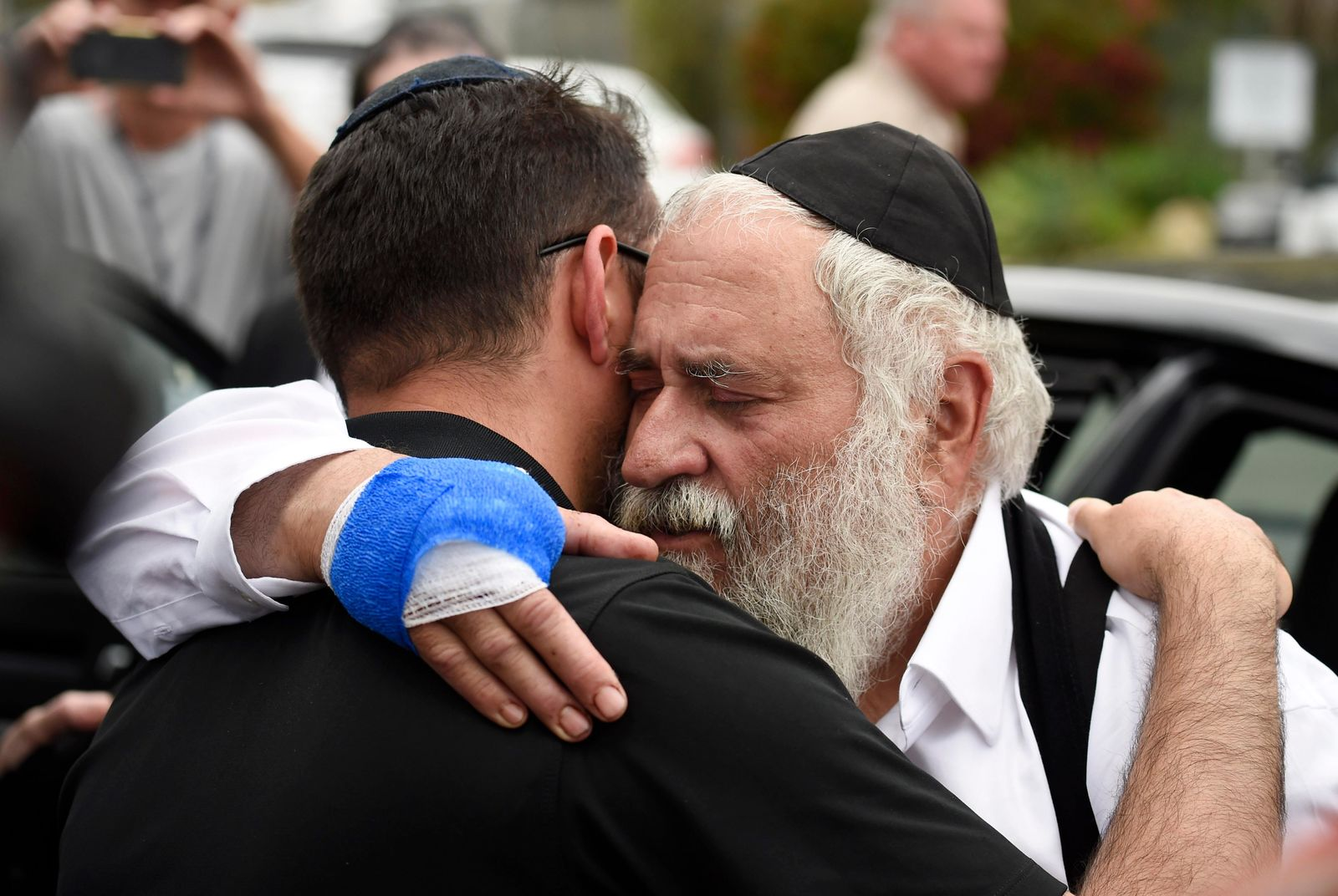 FILE - In this April 28, 2019, file, photo, Rabbi Yisroel Goldstein, right, is hugged as he leaves a news conference at the Chabad of Poway synagogue in Poway, Calif. (AP Photo/Denis Poroy, File)