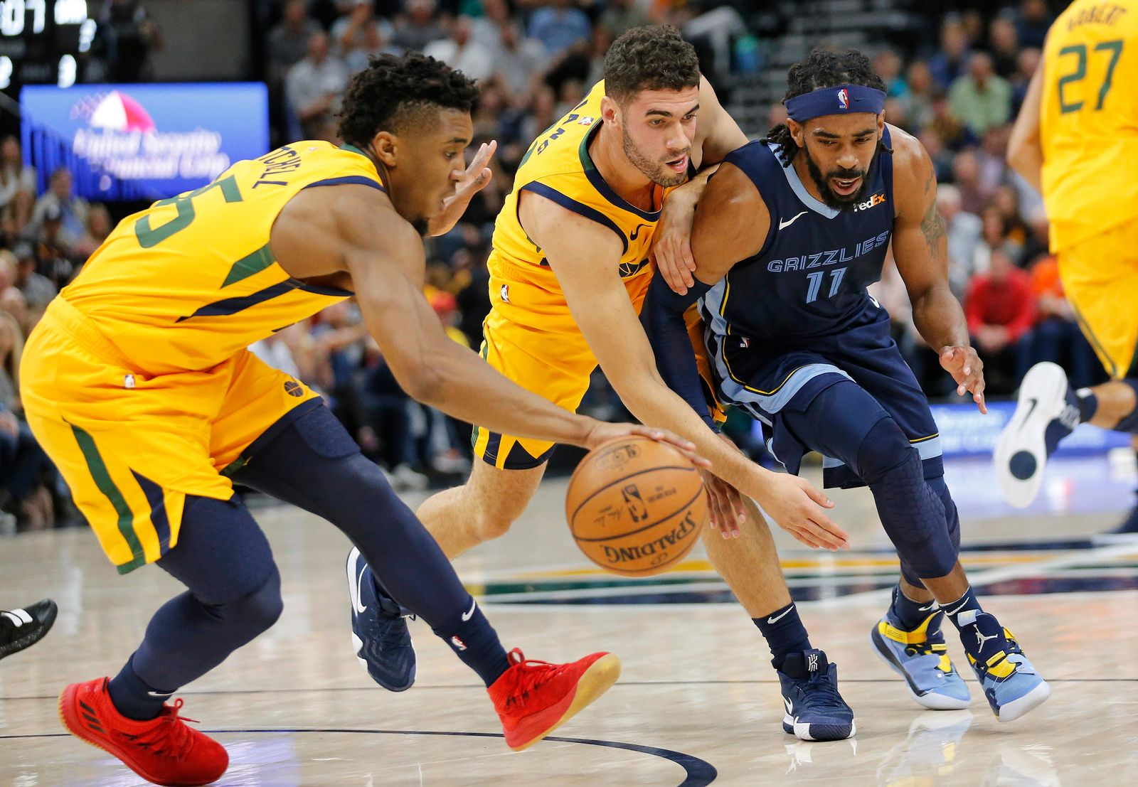 Utah Jazz's Donovan Mitchell, left, steals the ball as teammate Georges Niang, center, defends Memphis Grizzlies guard Mike Conley (11) in the first half of an NBA basketball game, Monday, Oct. 22, 2018, in Salt Lake City. (AP Photo/Rick Bowmer)