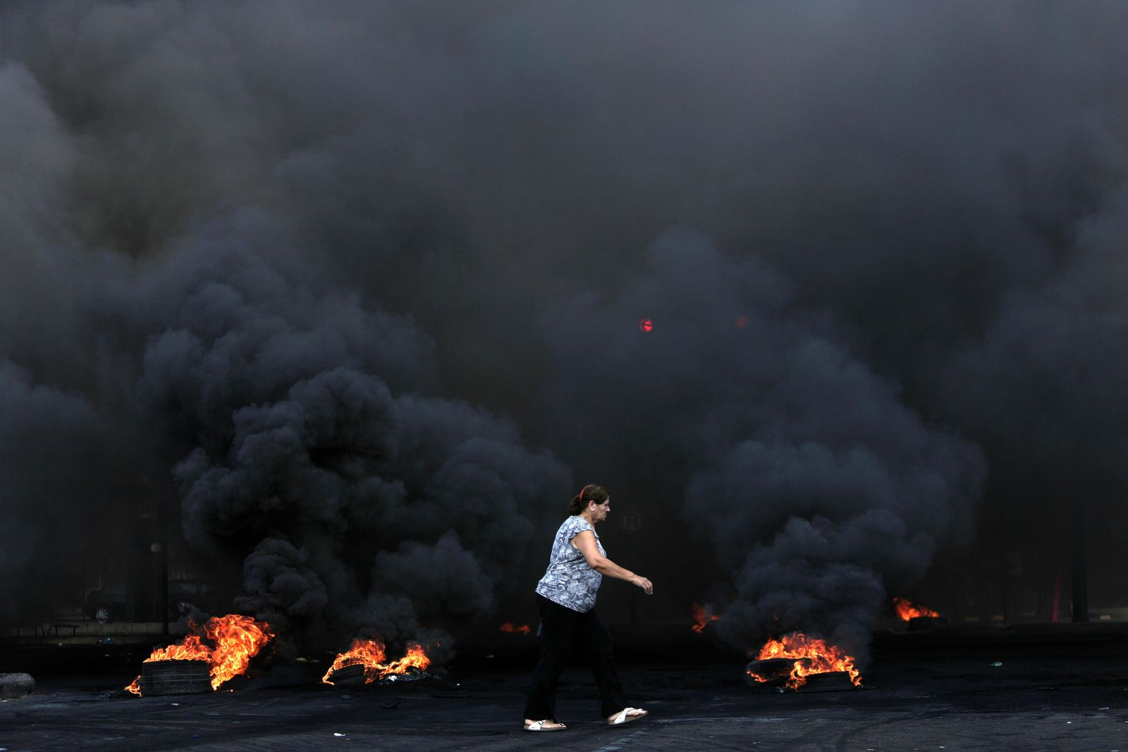 A woman walks by burning tires that were set fire to block a road during a protest against government's plans to impose new taxes in Beirut, Lebanon, Friday, Oct. 18, 2019. (AP Photo/Hassan Ammar)