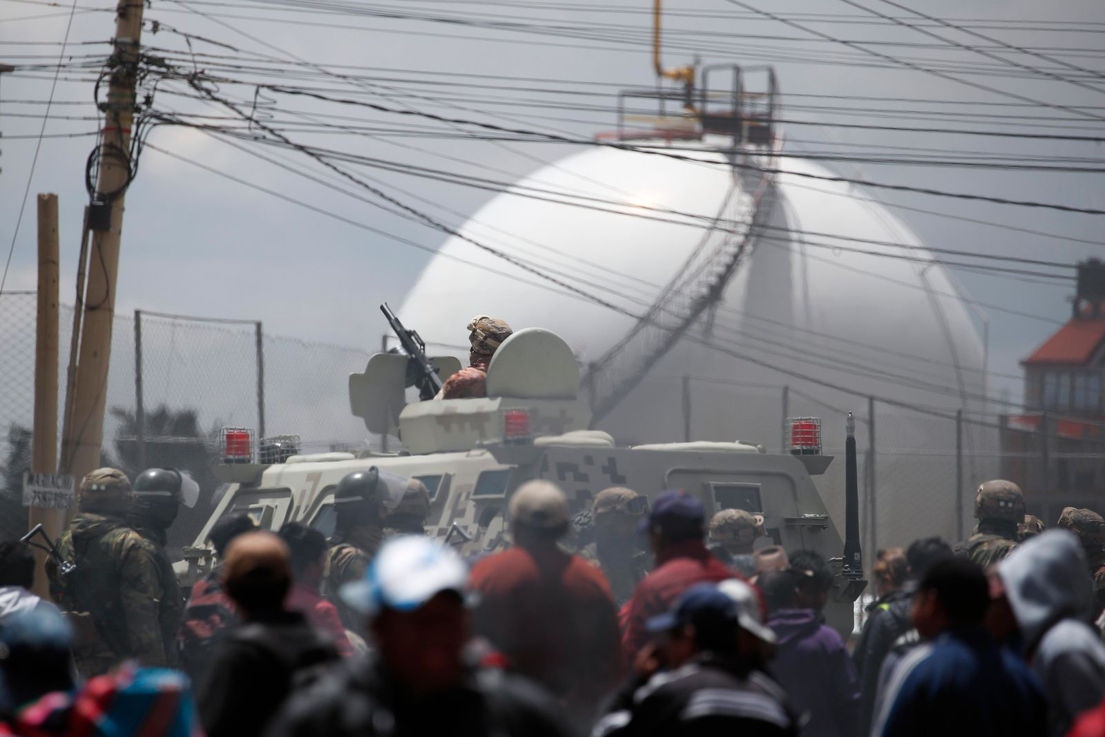 Soldiers guard the perimeters of the state-own Senkata filling plant, as supporters of former President Evo Morales gather round, in El Alto, on the outskirts of La Paz, Bolivia, Tuesday, Nov. 19, 2019.{ } (AP Photo/Natacha Pisarenko)