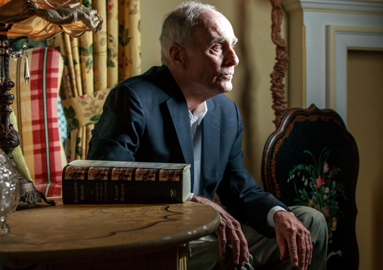 "FILE - In this March 7, 2013 file photo, former Los Angeles prosecutor Vincent Bugliosi sits next to his book: ""Reclaiming History: The Assassination of President John F. Kennedy"" at his home in Pasadena, Calif. (AP Photo/Damian Dovarganes, File)"