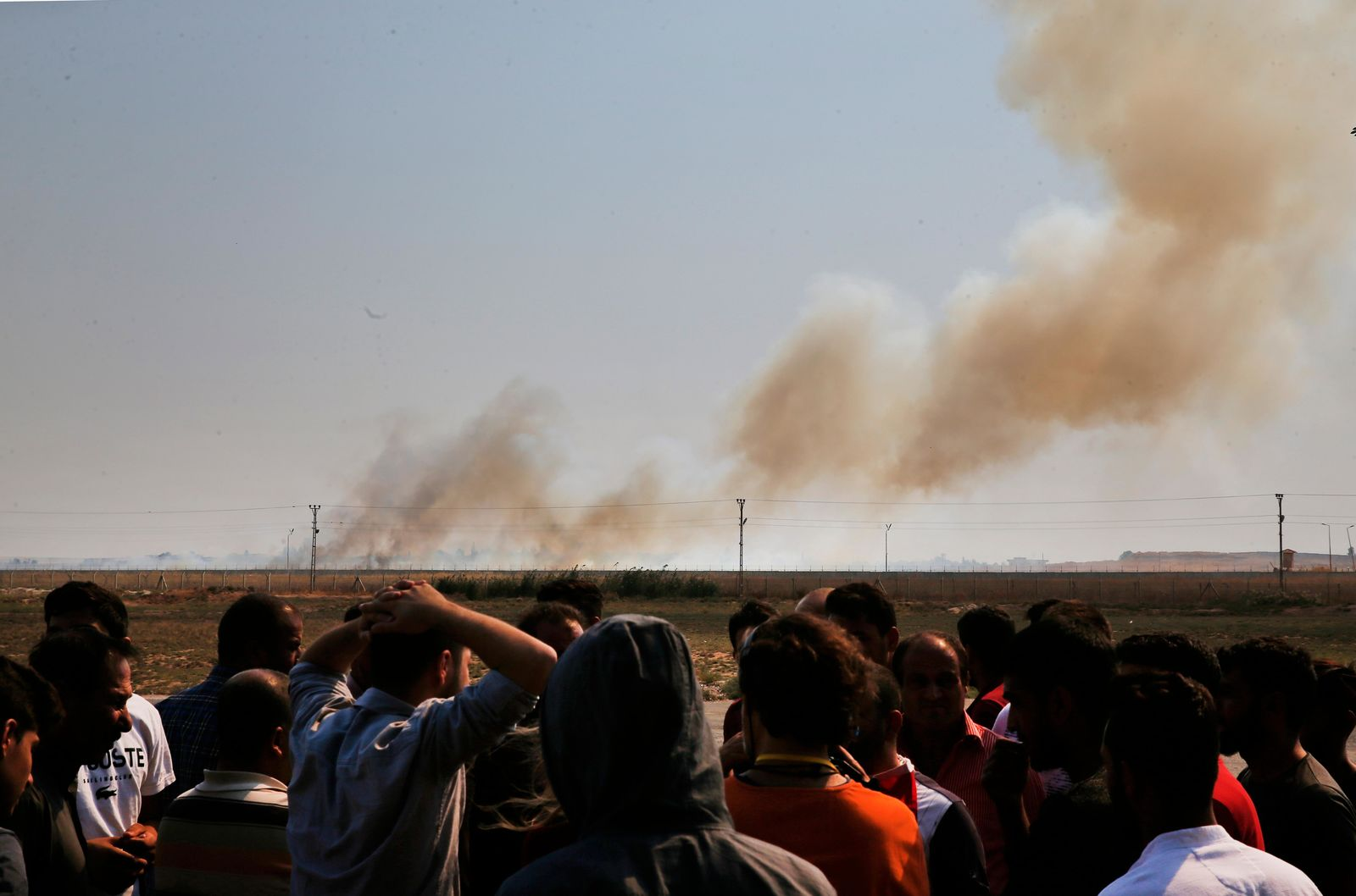 People watch from Akcakale, Sanliurfa province, southeastern Turkey, as smoke billows from fires on targets in Tel Abyad, Syria, caused by bombardment by Turkish forces, Sunday, Oct. 13, 2019. (AP Photo/Lefteris Pitarakis)