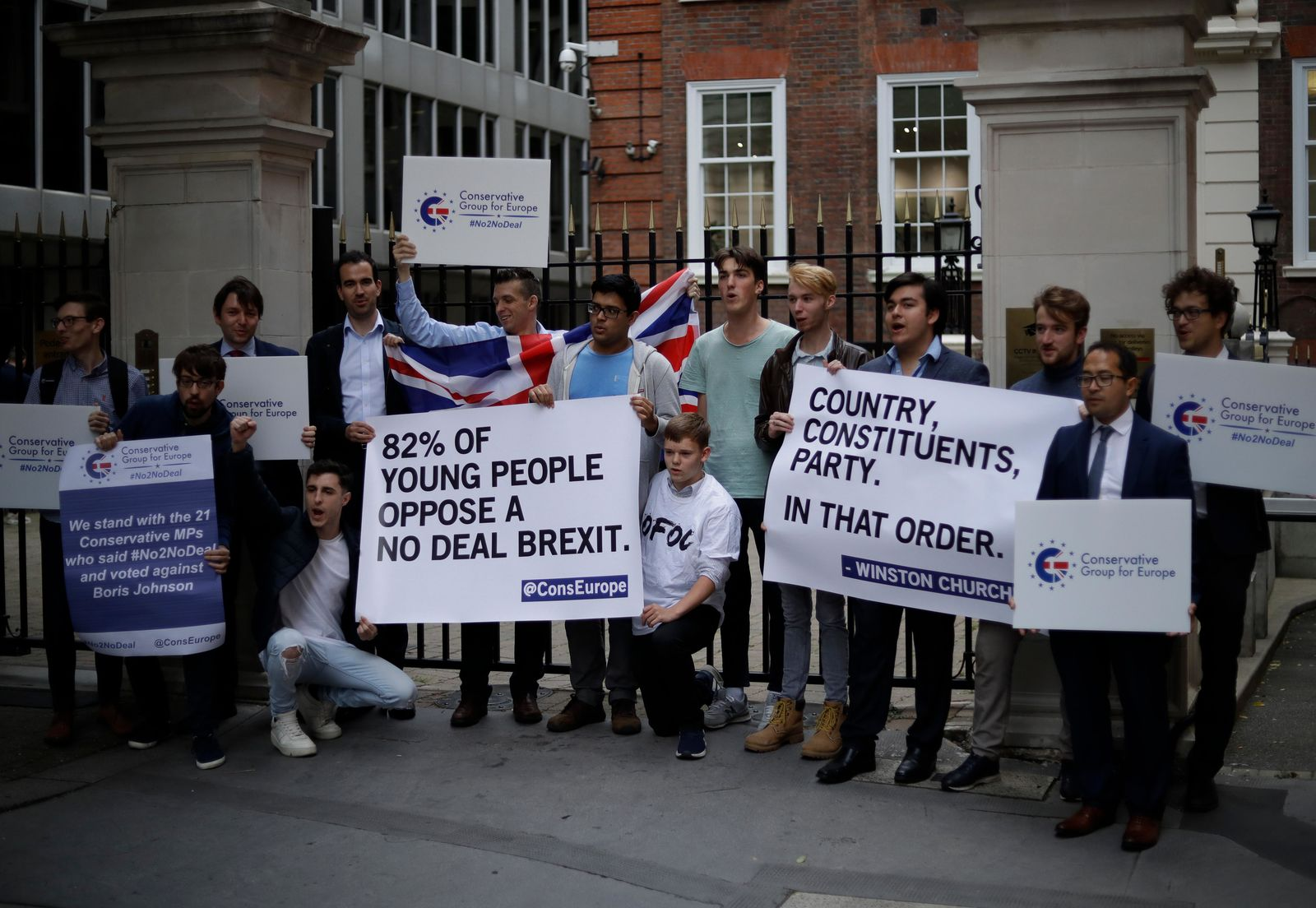 Young Conservative party members hold signs as they demonstrate outside Conservative Party Campaign Headquarters in London, Wednesday, Sept. 4, 2019. (AP Photo/Matt Dunham)
