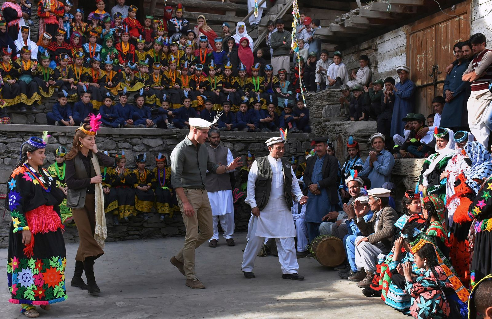 In this photo released by Press Information Department, Britain's Prince William, center, and his wife Kate interact with the members of Kalash community during their visit to Bumburate Valley, an area of Pakistan's northern Chitral district, Wednesday Oct. 16, 2019. (Press Information Department via AP)