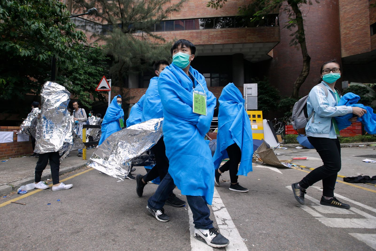 Injured protesters wrapped in blankets, walk through the campus of the Hong Kong Polytechnic University in Hong Kong, Tuesday, Nov. 19, 2019.. (AP Photo/Achmad Ibrahim)