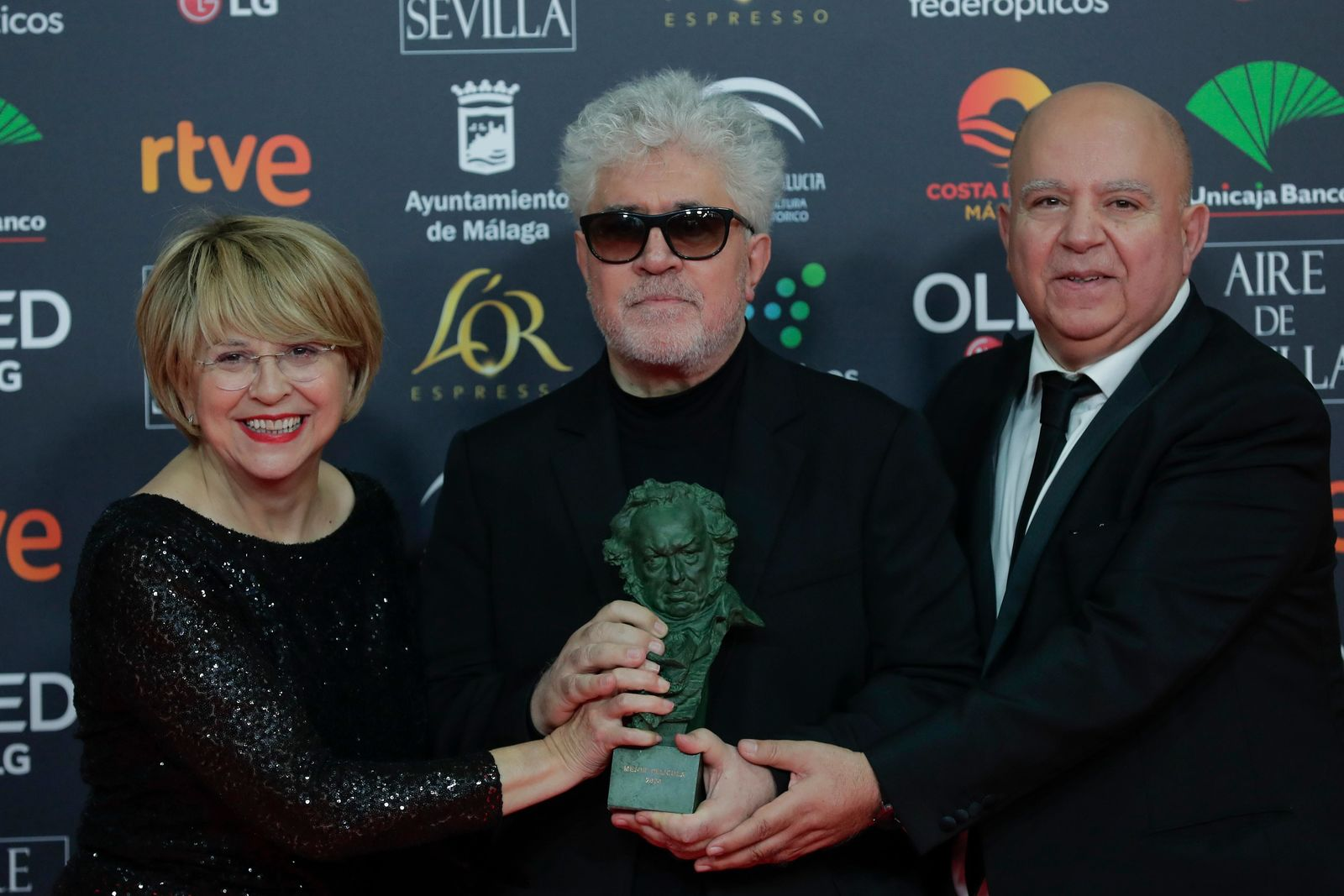 "Spanish film director Pedro Almodovar, center, and producers Agustin Almodovar and Esther Garcia, left, pose with their trophy after winning the best film award for ""Dolor y gloria"" during the Goya Film Awards Ceremony in Malaga, southern Spain, early Sunday, Jan. 26, 2020. The annual Goya Awards are Spain's main national film awards. (AP Photo/Manu Fernandez)"