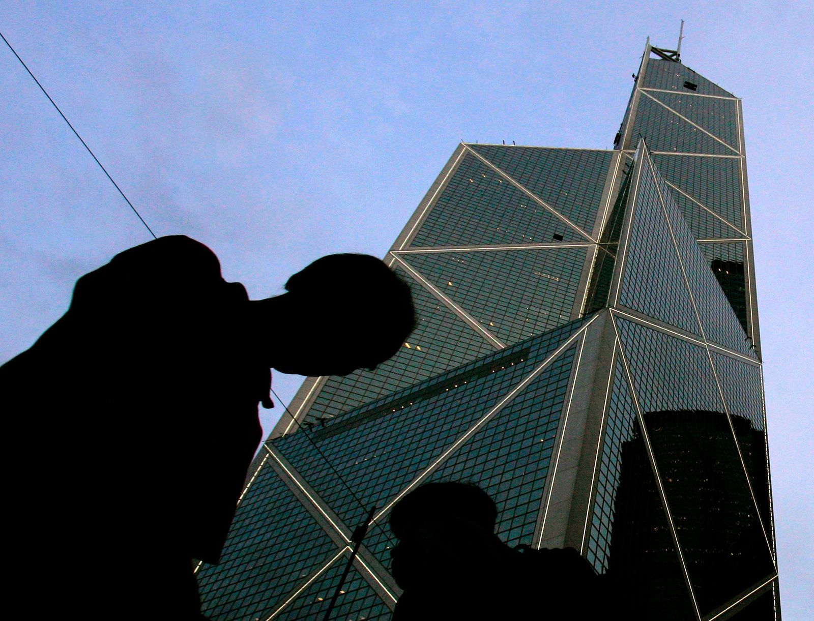 FILE - In this Friday, May 19, 2006, file photo, pedestrians walk past the Bank of China building in Hong Kong, designed by American architect I.M. Pei. Pei, the globe-trotting architect who revived the Louvre museum in Paris with a giant glass pyramid and captured the spirit of rebellion at the multi-shaped Rock and Roll Hall of Fame, has died at age 102, a spokesman confirmed Thursday, May 16, 2019. (AP Photo/Kin Cheung, File)