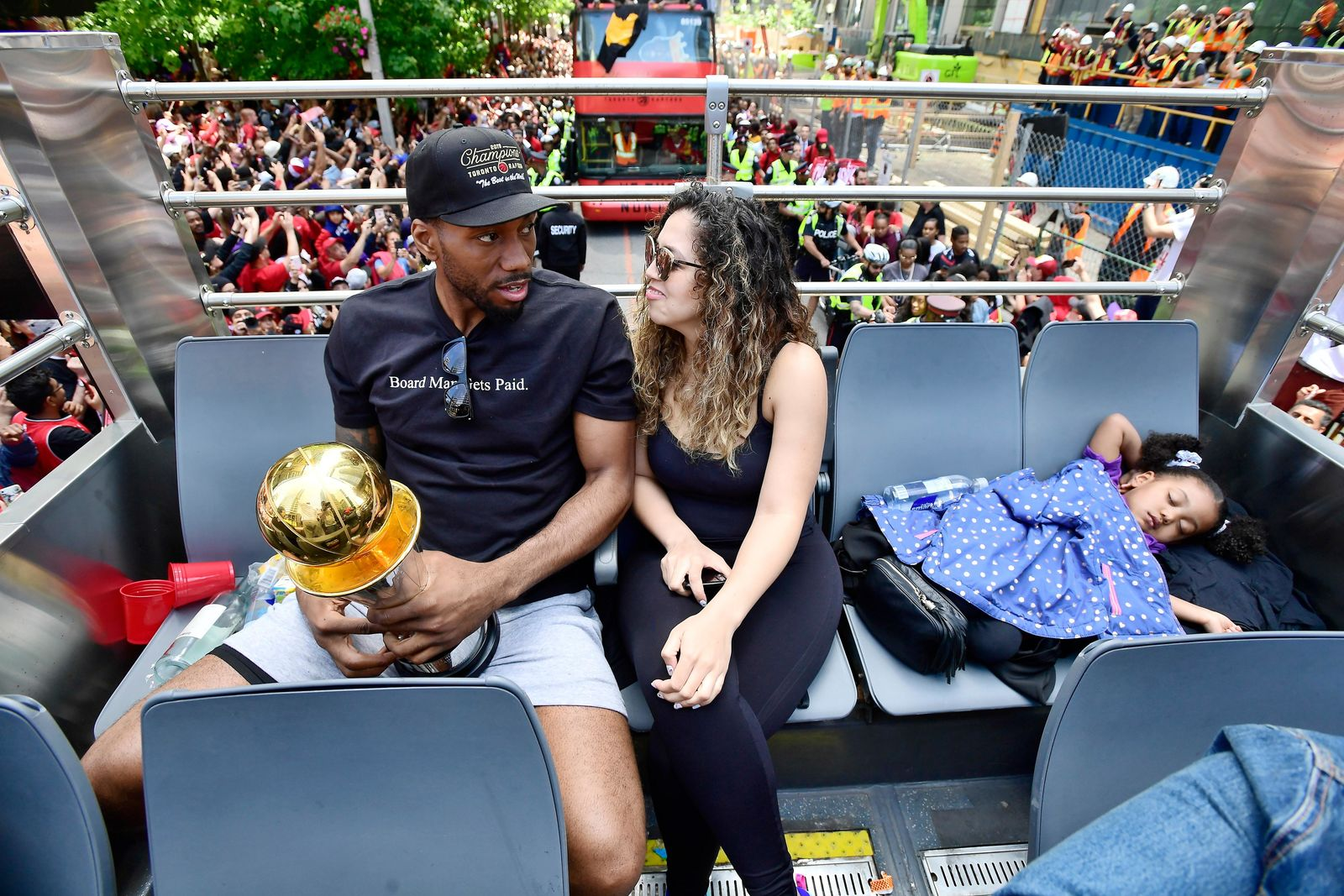 Toronto Raptors forward Kawhi Leonard and his girlfriend Kishele Shipley take a seat as their daughter Kaliyah naps during the NBA basketball championship team's victory parade in Toronto, Monday, June 17, 2019. (Frank Gunn/The Canadian Press via AP)