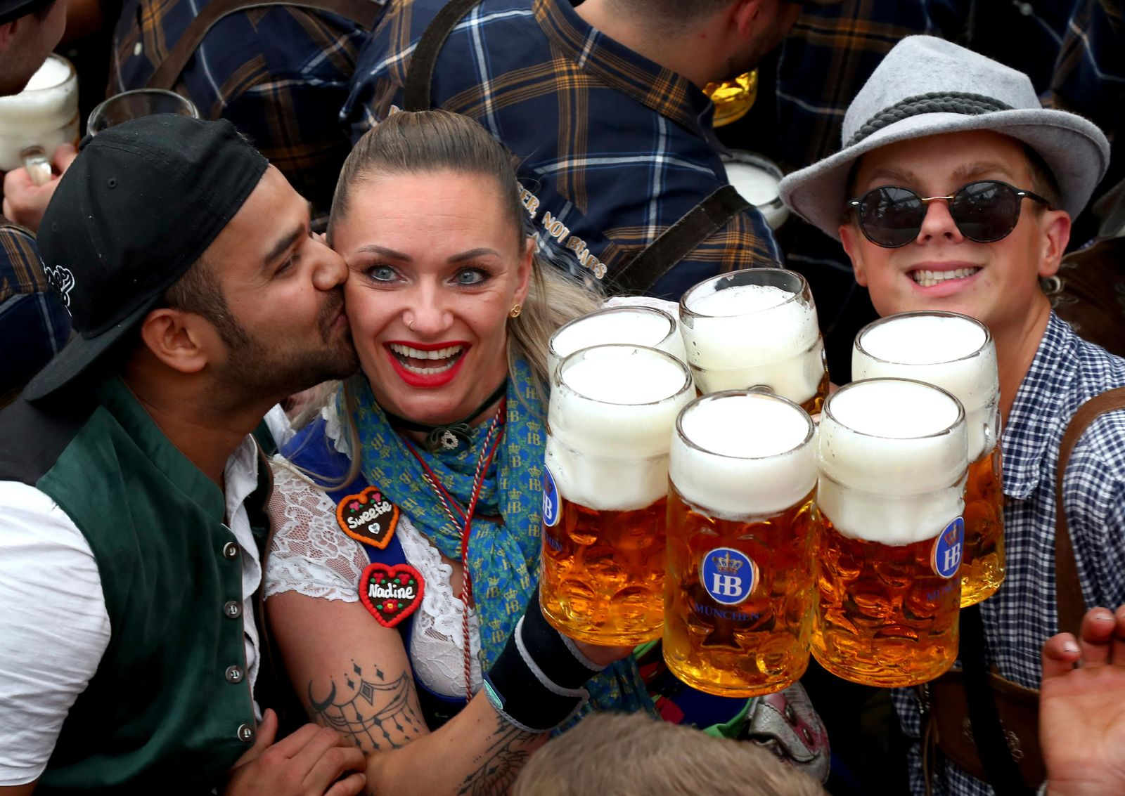 A waitress is kissed by a guest as she holds glasses of beer during the opening of the 186th 'Oktoberfest' beer festival in Munich, Germany, Saturday, Sept. 21, 2019. (AP Photo/Matthias Schrader)