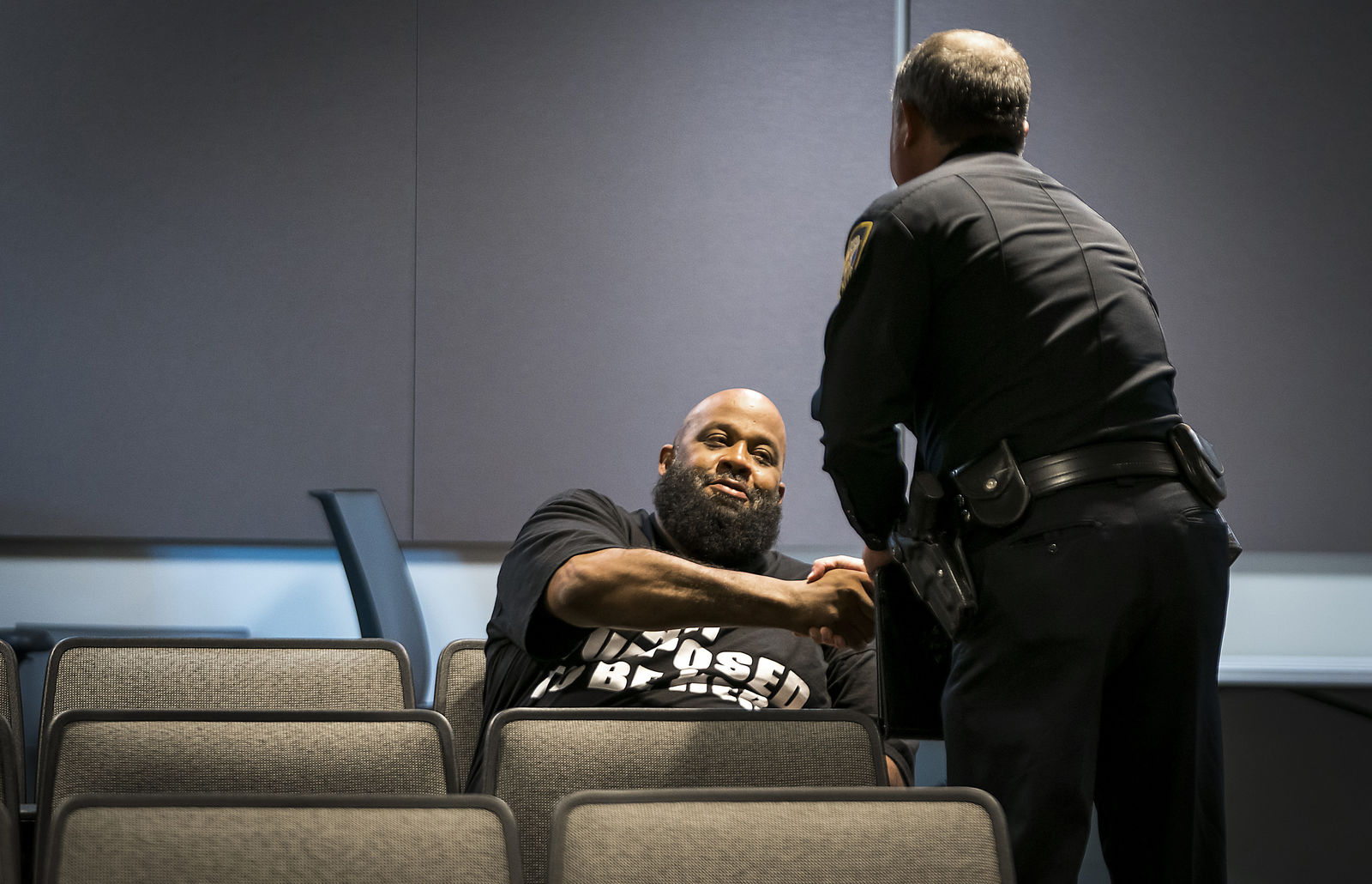Fort Worth Police Lt. Brandon O'Neil shakes hands with Roger Foggle after addressing a news conference regarding the shooting of Atatiana Jefferson at the Bob Bolen Public Safety Complex on Sunday, Oct. 13, 2019, in Fort Worth, Texas. (Smiley N. Pool/The Dallas Morning News via AP)