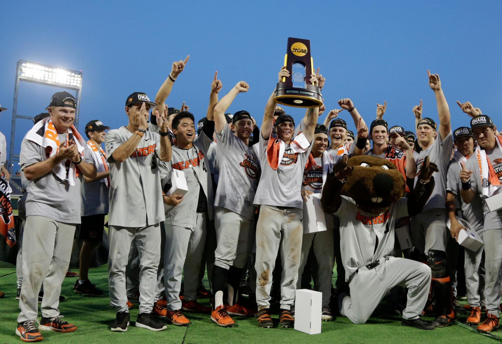 Oregon State players and coaches celebrate with their mascot and the trophy after they beat Arkansas 5-0 in Game 3 to win the NCAA College World Series baseball finals, Thursday, June 28, 2018, in Omaha, Neb. (AP Photo/Nati Harnik)