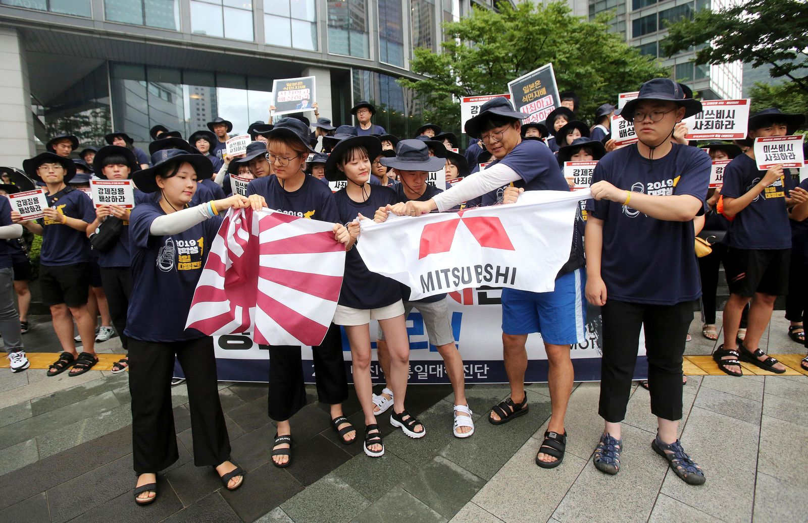 South Korean college students tear banners showing an image of a Japanese rising sun flag and the logo of Mitsubishi Corp. during a rally to denounce Japan's new trade restrictions on South Korea in front of the office of Mitsubishi Corp. in Seoul, South Korea, Wednesday, Aug. 7, 2019.{ } (AP Photo/Ahn Young-joon)