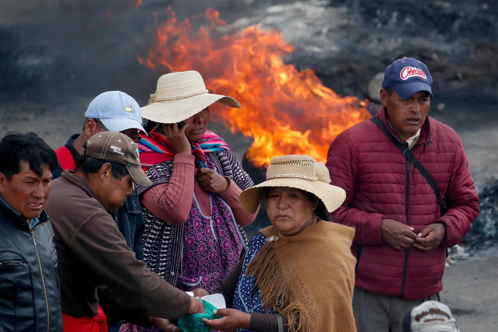 Supporters of former President Evo Morales chew coca leaves at a barricade in El Alto, on the outskirts of La Paz, Bolivia, Tuesday, Nov. 19, 2019. (AP Photo/Natacha Pisarenko)