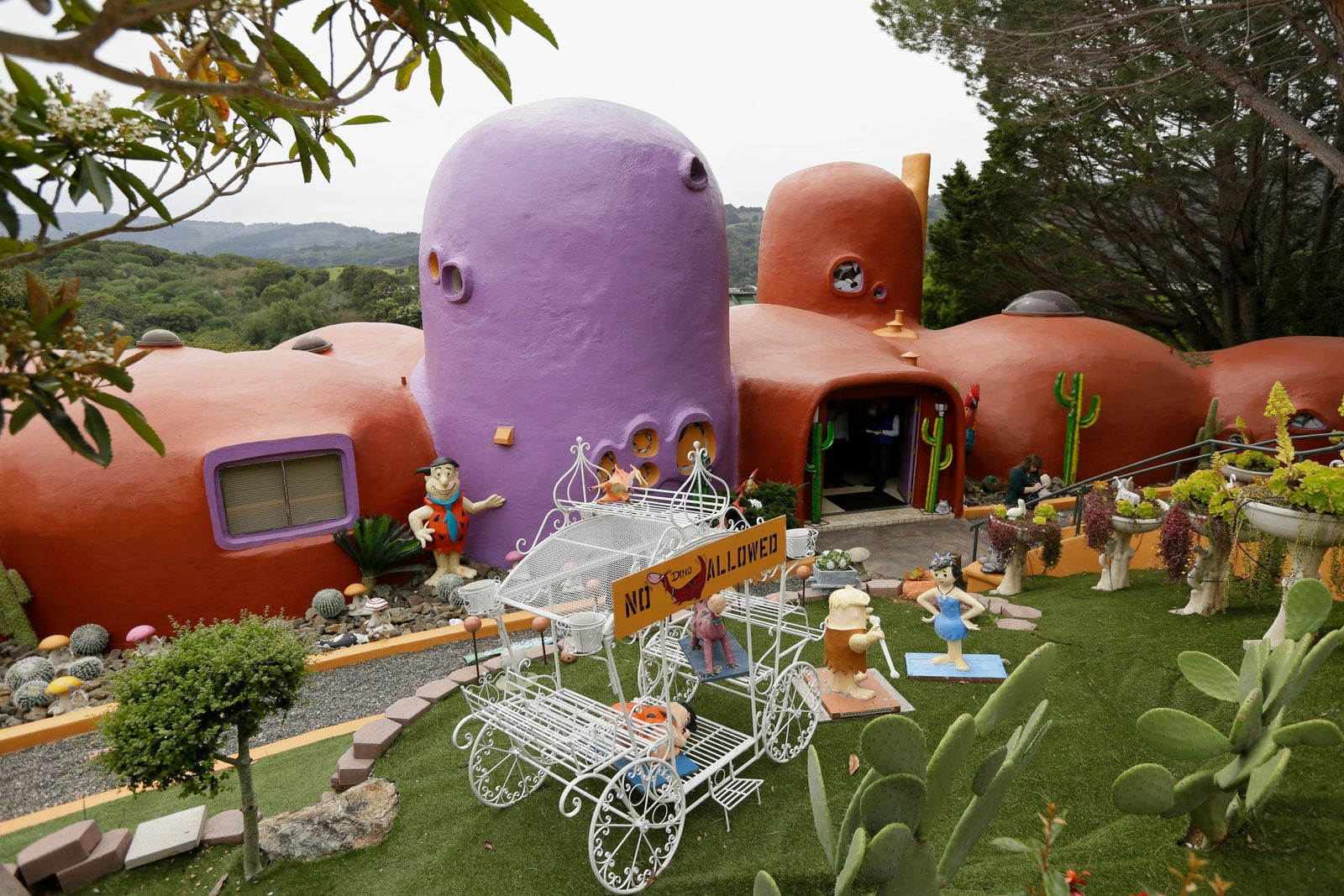 In this photo taken Monday, April 1, 2019, is an exterior view of the Flintstone House in Hillsborough, Calif. The San Francisco Bay Area suburb of Hillsborough is suing the owner of the house, saying that she installed dangerous steps, dinosaurs and other Flintstone-era figurines without necessary permits.   (AP Photo/Eric Risberg)