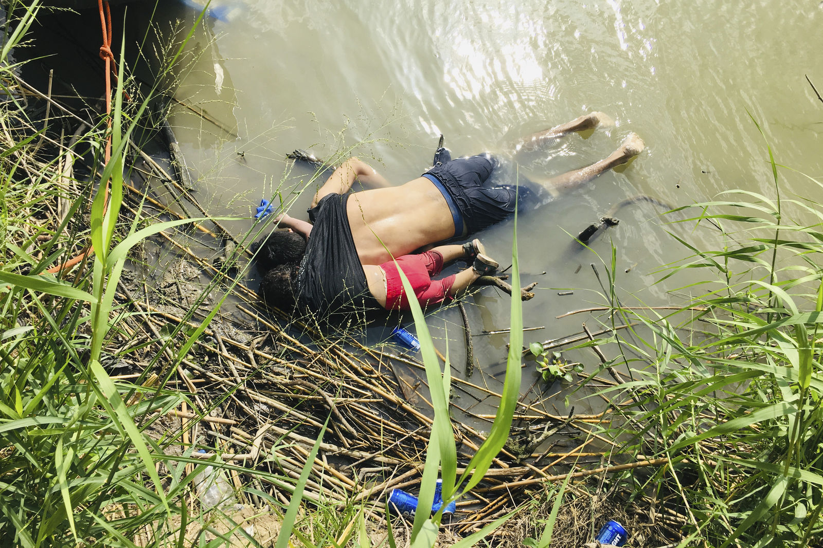 WARNING GRAPHIC CONTENT - The bodies of Salvadoran migrant Oscar Alberto Martínez Ramírez and his nearly 2-year-old daughter Valeria lie on the bank of the Rio Grande in Matamoros, Mexico, Monday, June 24, 2019, after they drowned trying to cross the river to Brownsville, Texas. Martinez' wife, Tania told Mexican authorities she watched her husband and child disappear in the strong current. (AP Photo/Julia Le Duc)