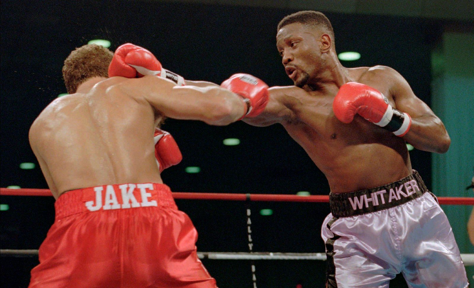 "FILE - In this Nov. 18, 1995, file photo, WBC welterweight champion Pernell ""Sweet Pea"" Whitaker, right, delivers a right to the head of challenger Jake Rodriguez during their scheduled 12 round bout in Atlantic City, N.J. (AP Photo/Donna Connor, File)"