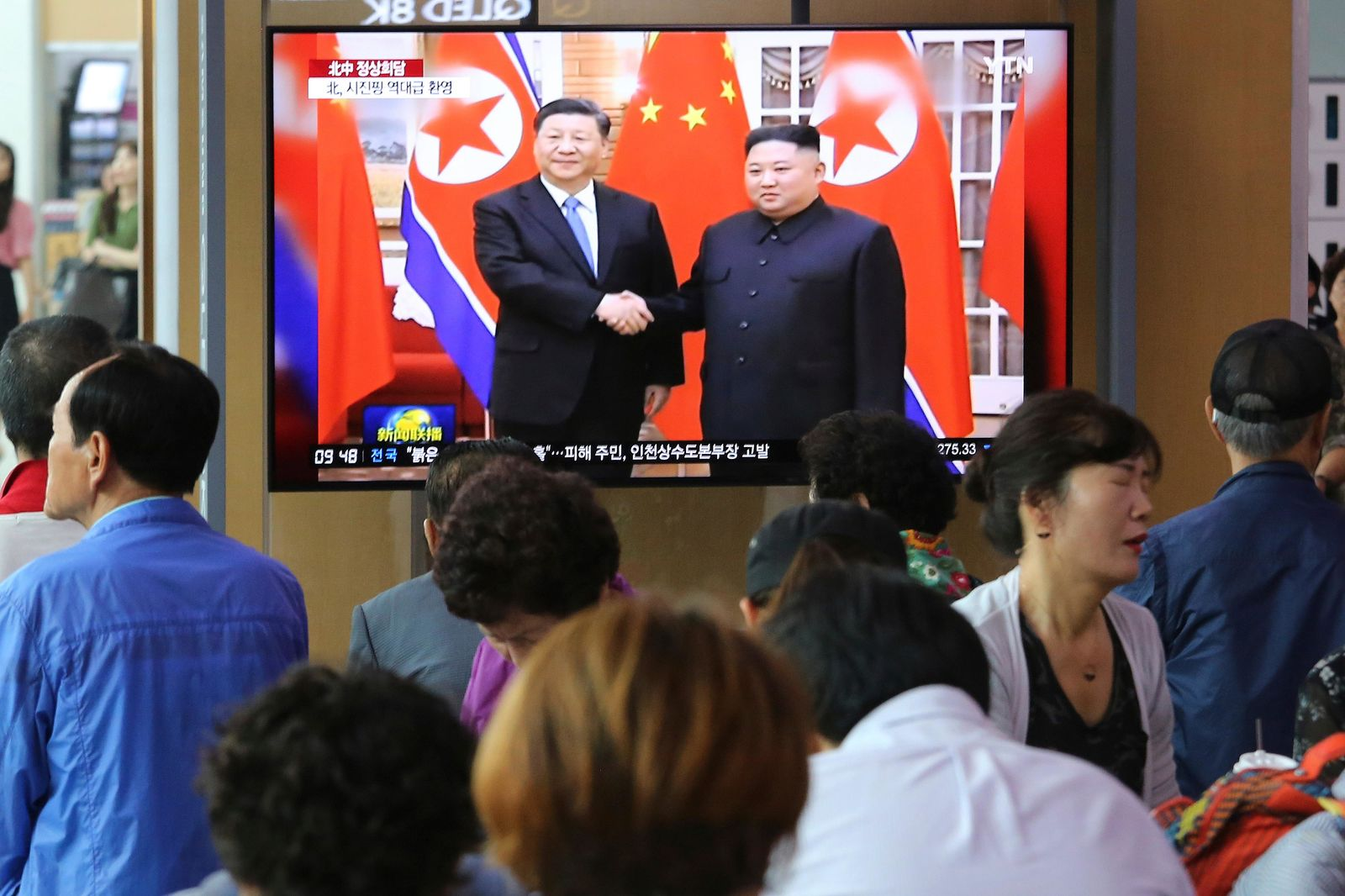 "People watch a TV screen showing North Korean leader Kim Jong Un, right, welcoming Chinese President Xi Jinping, at the Seoul Railway Station in Seoul, South Korea, Friday, June 21, 2019. North Korea's state media says leader Kim Jong Un and Chinese President Xi Jinping held broad discussions over the political situation surrounding the Korean Peninsula and called for stronger bilateral ties in the face of ""serious and complicated changes"" in the region. (AP Photo/Ahn Young-joon)"