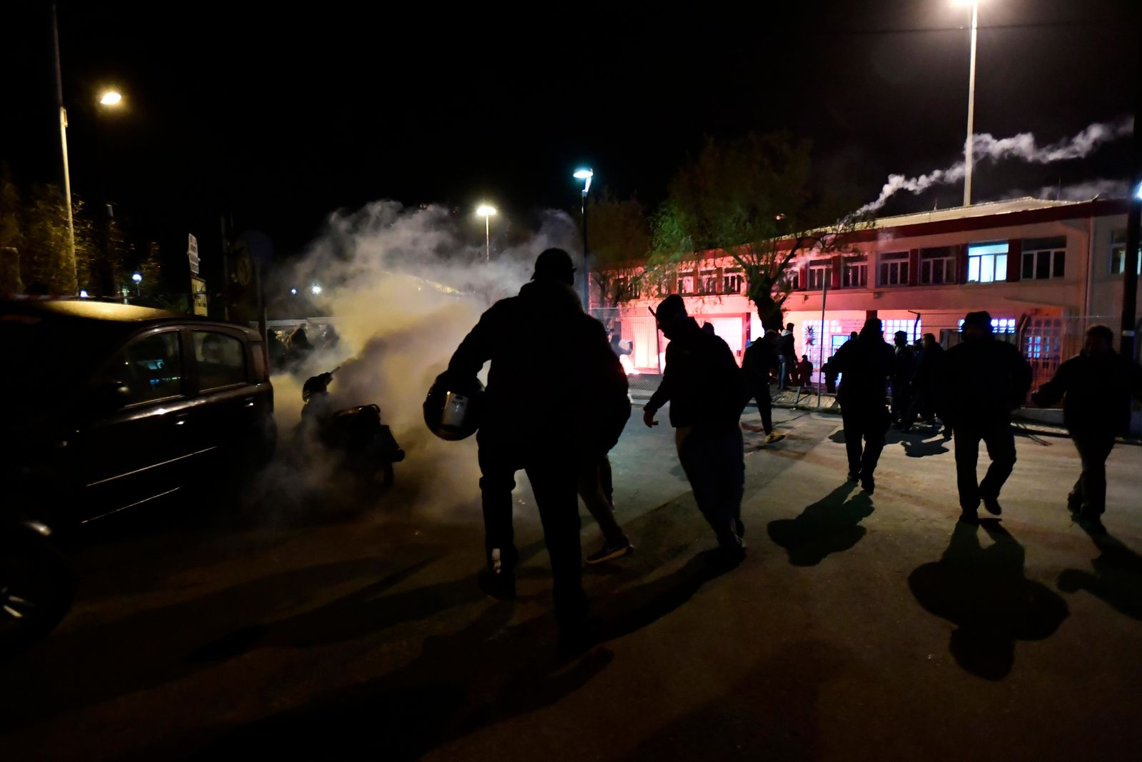 Riot police throw teat gas at local residents during clashes at the port of Mytilene on the northeastern Aegean island of Lesbos, Greece, early Tuesday, Feb. 25, 2020.{ } (AP Photo/Michael Varaklas)