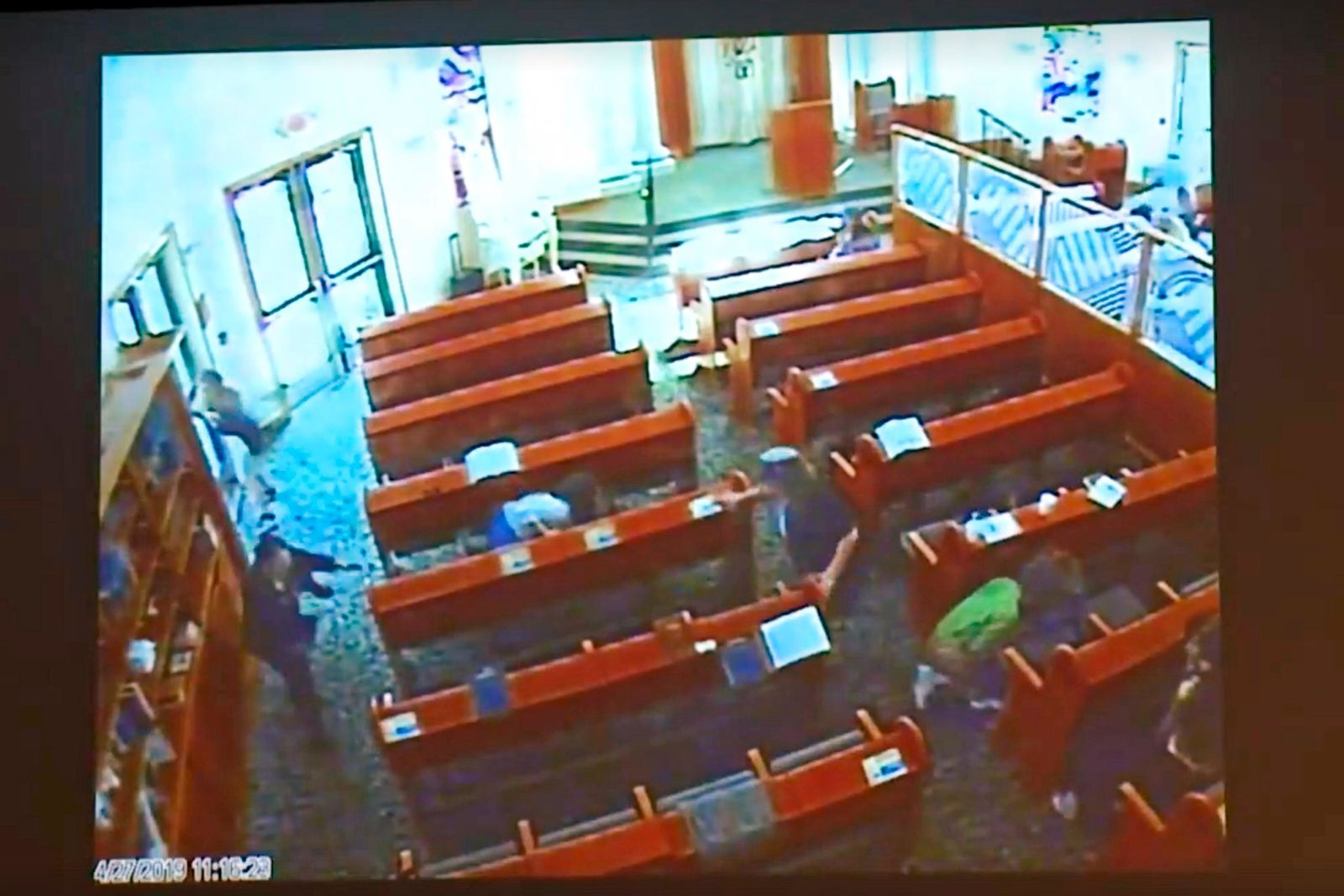 This April 27, 2019 photo from surveillance video at the Chabad of Poway, shown as evidence in the preliminary hearing of John T. Earnest, shows people diving for cover during during what authorities say is Earnest's rampage on the synagogue in Poway, Calif., in court in San Diego, Calif. on Thursday, Sept. 19, 2019. A woman was killed and three other people were wounded in the attack. Earnest has pleaded not guilty to murder, attempted murder and arson tied to a mosque fire. (Chabad of Poway/San Diego Superior Court via AP)