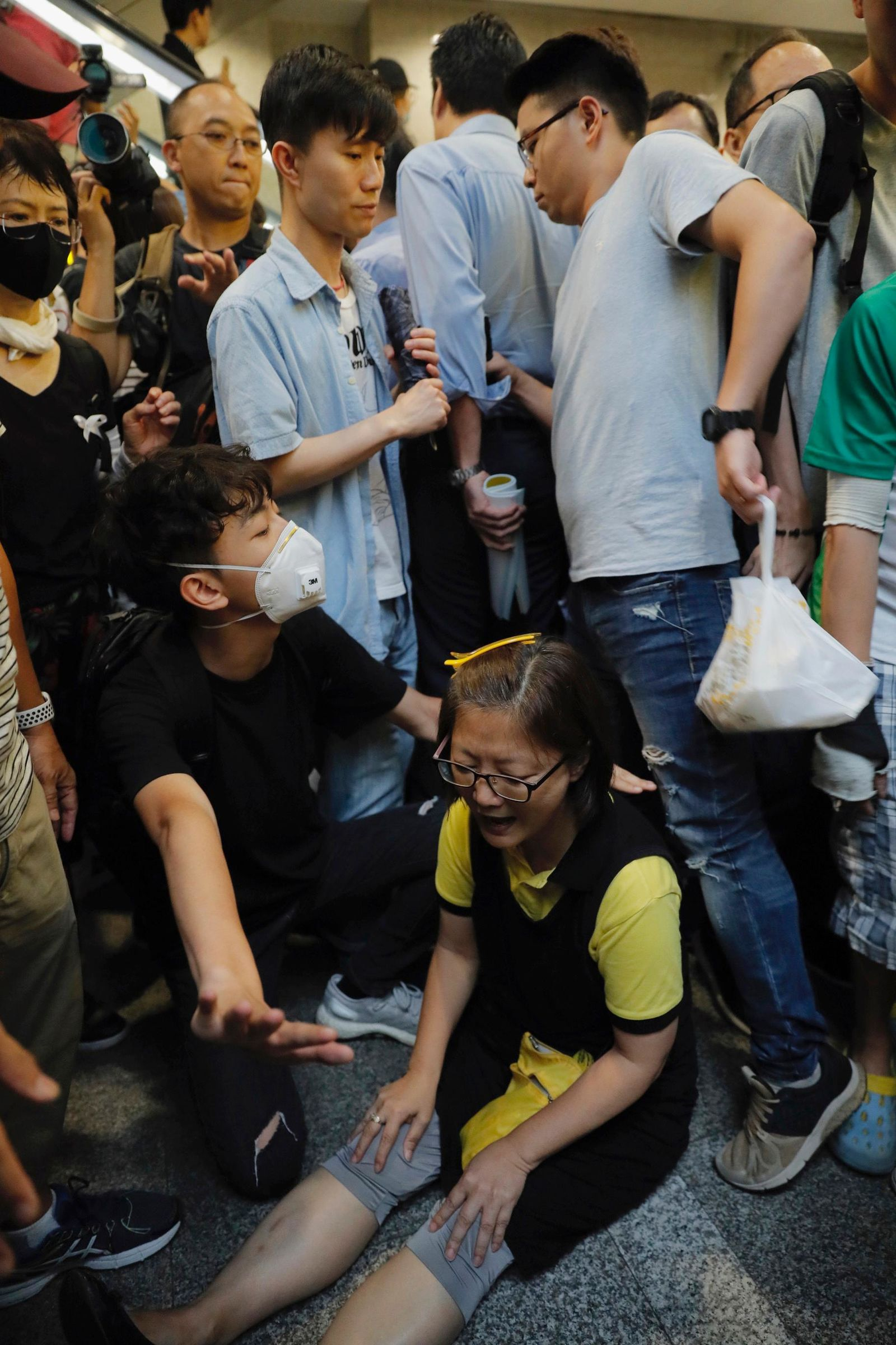 A protester sits down to block visitors in the lobby of the Hong Kong Revenue Tower in Hong Kong on Monday, June 24, 2019.{ } (AP Photo/Kin Cheung)