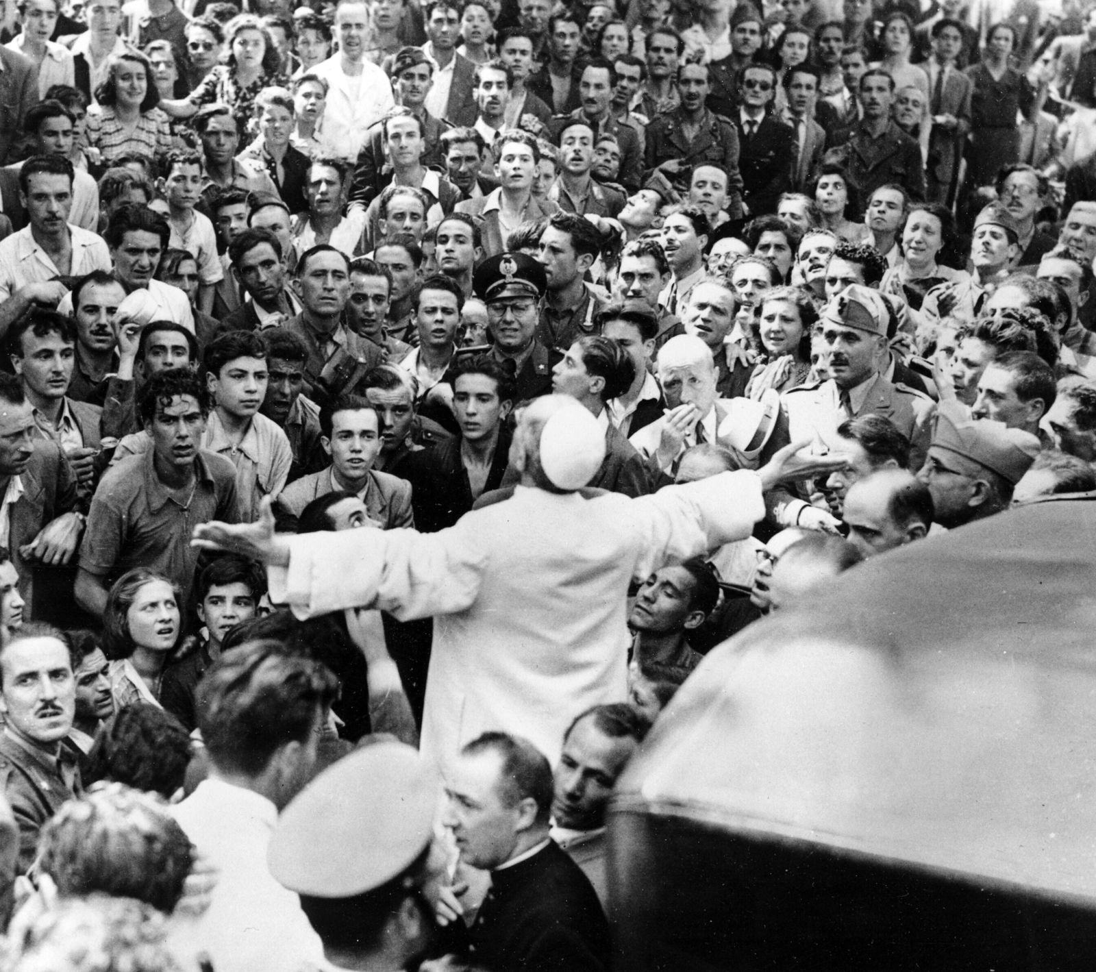 In this Oct. 15, 1943 file photo, men, women and soldiers gather around Pope Pius XII, his arms outstretched, during his inspection tour of Rome, Italy, after the Aug. 13 American air raid during World War II. The Vatican's chief librarian and archivists said Thursday, Feb. 20, 2020 that all researchers _ regardless of nationality, faith and ideology _ were welcome to request access to the soon-to-open Vatican's apostolic library on Pope Pius XII starting March 2.  (AP Photo, file)