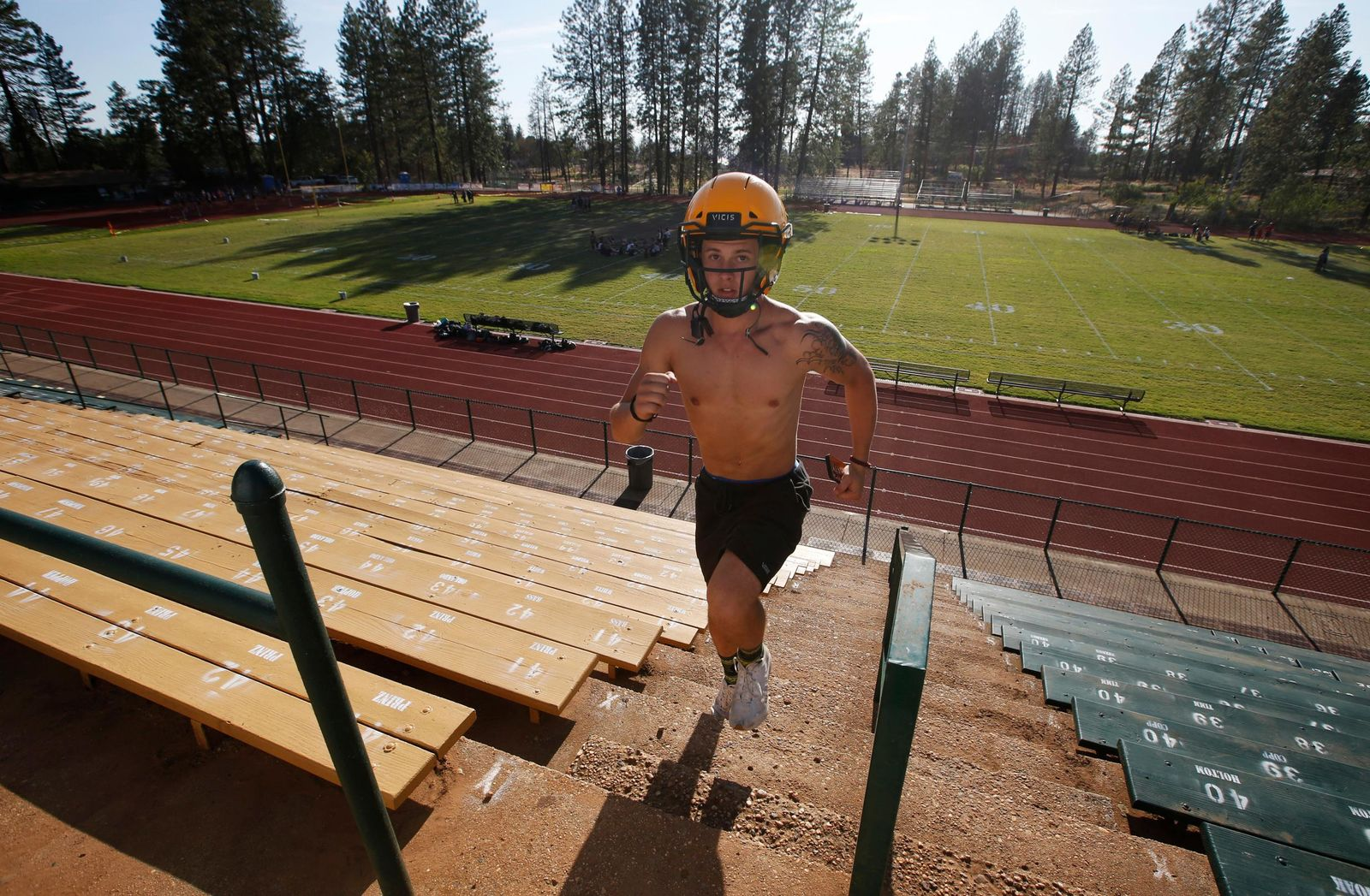 In this Thursday, Aug. 22, 2019, photo, Paradise High School football player Lukas Hartley runs up the stairs of the football stadium after practice in Paradise, Calif.{ } (AP Photo/Rich Pedroncelli)