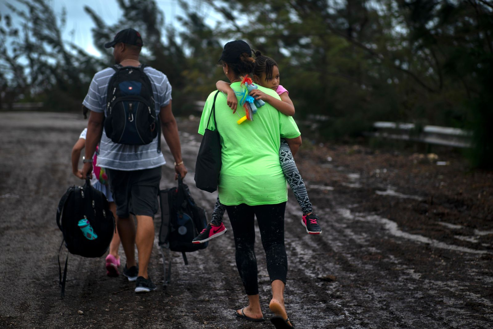 A family walks on a road after being rescued from the flood waters of Hurricane Dorian, near Freeport, Grand Bahama, Bahamas, Tuesday Sept. 3, 2019. They were rescued by volunteers who drove a bus into the flood waters to pick them up. (AP Photo/Ramon Espinosa)