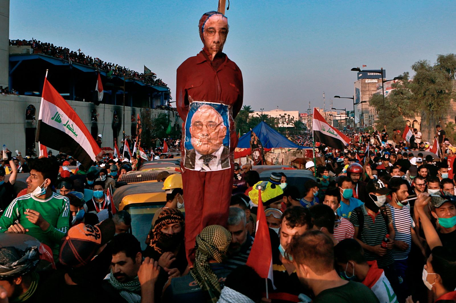 FILE - in this Wednesday, Oct. 30, 2019 file photo, Anti-government protesters hold an effigy of Iraqi Prime Minister Adel Abdel-Mahdi during ongoing protests in Baghdad, Iraq. Celebrations have erupted in Iraq's Tahrir Square, Friday, Nov. 29, where anti-government protesters have been camped out for nearly two months following an announcement by Iraqi Prime Minister Adel Abdul-Mahdi, would be resigning. (AP Photo/Khalid Mohammed, File)