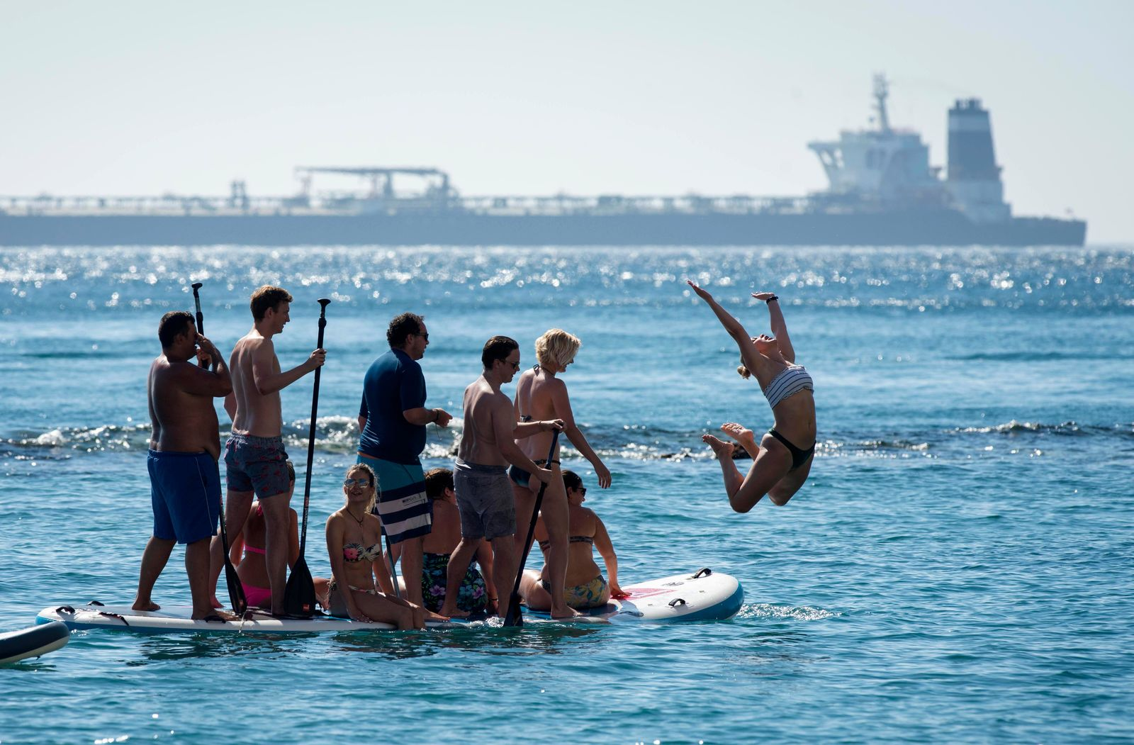 Renamed Adrian Aryra 1 super tanker is seen in background as people cool-off in the water in the British territory of Gibraltar, Sunday, Aug. 18, 2019.{ } (AP Photo/Marcos Moreno)