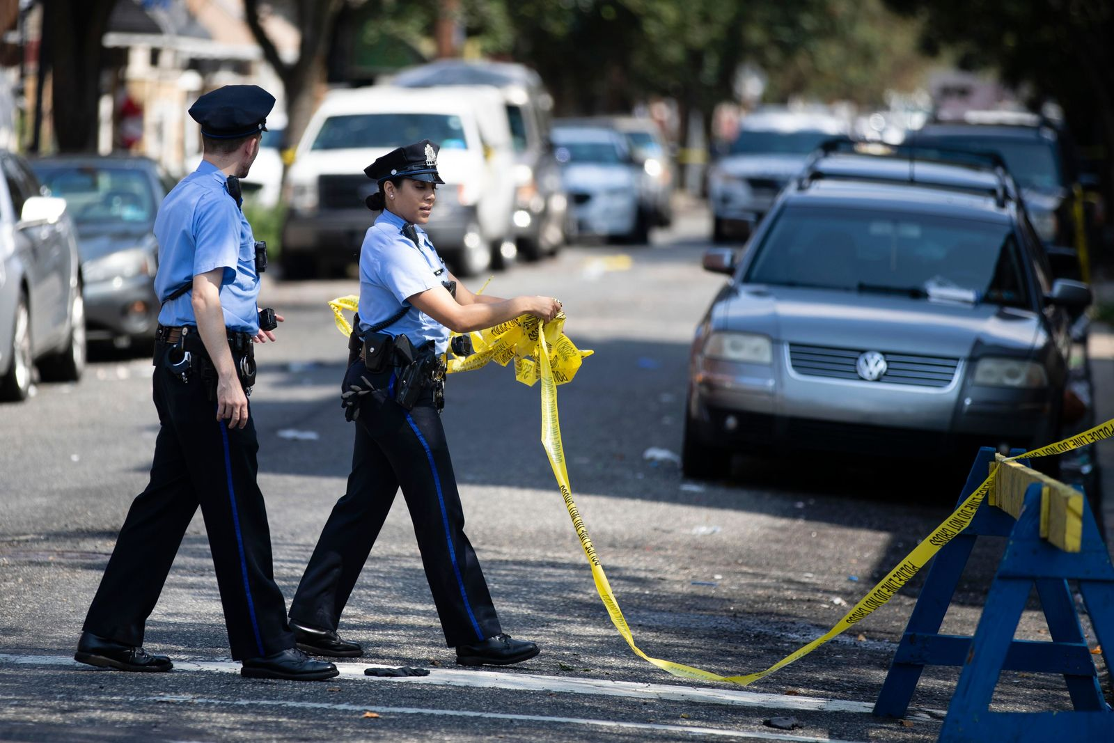 Officers move tape at the scene of Wednesday's standoff with police in Philadelphia, Thursday, Aug. 15, 2019. The gunman, identified as Maurice Hill, wounded six police officers before surrendering early Thursday, after a 7 ½-hour standoff. (AP Photo/Matt Rourke)