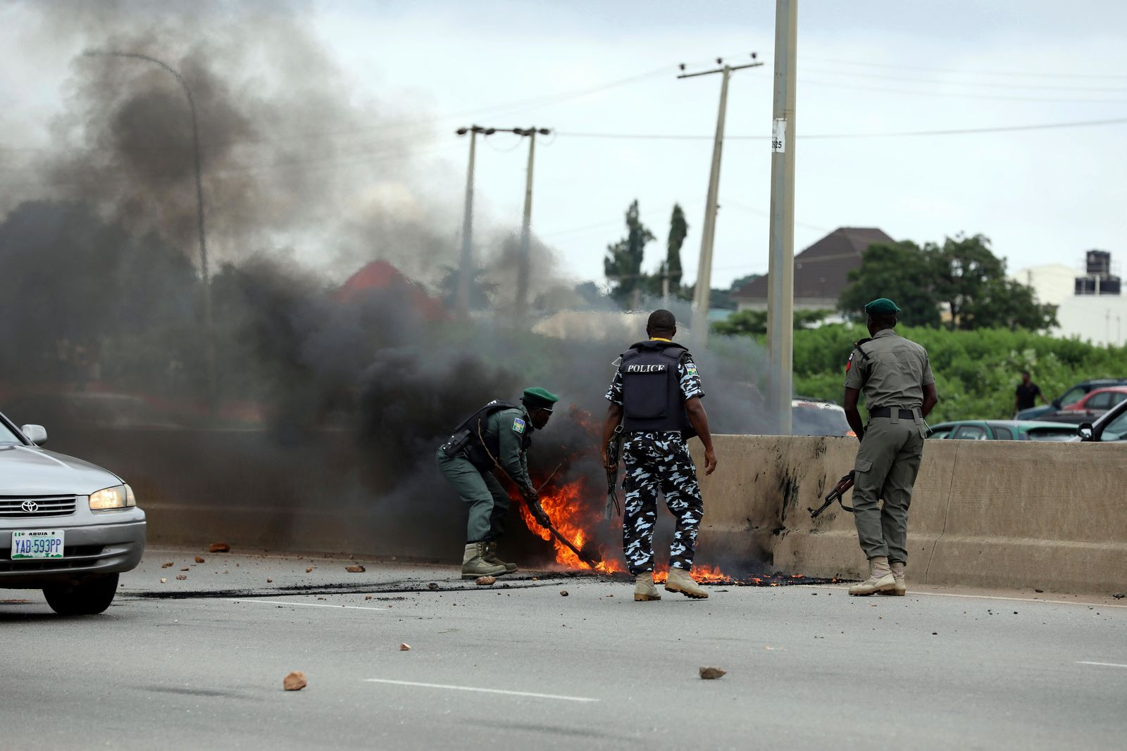 Policemen put out a bonfire set by protesters during a protest in Abuja, Nigeria Wednesday Sept. 4, 2019.{ } (AP Photo)