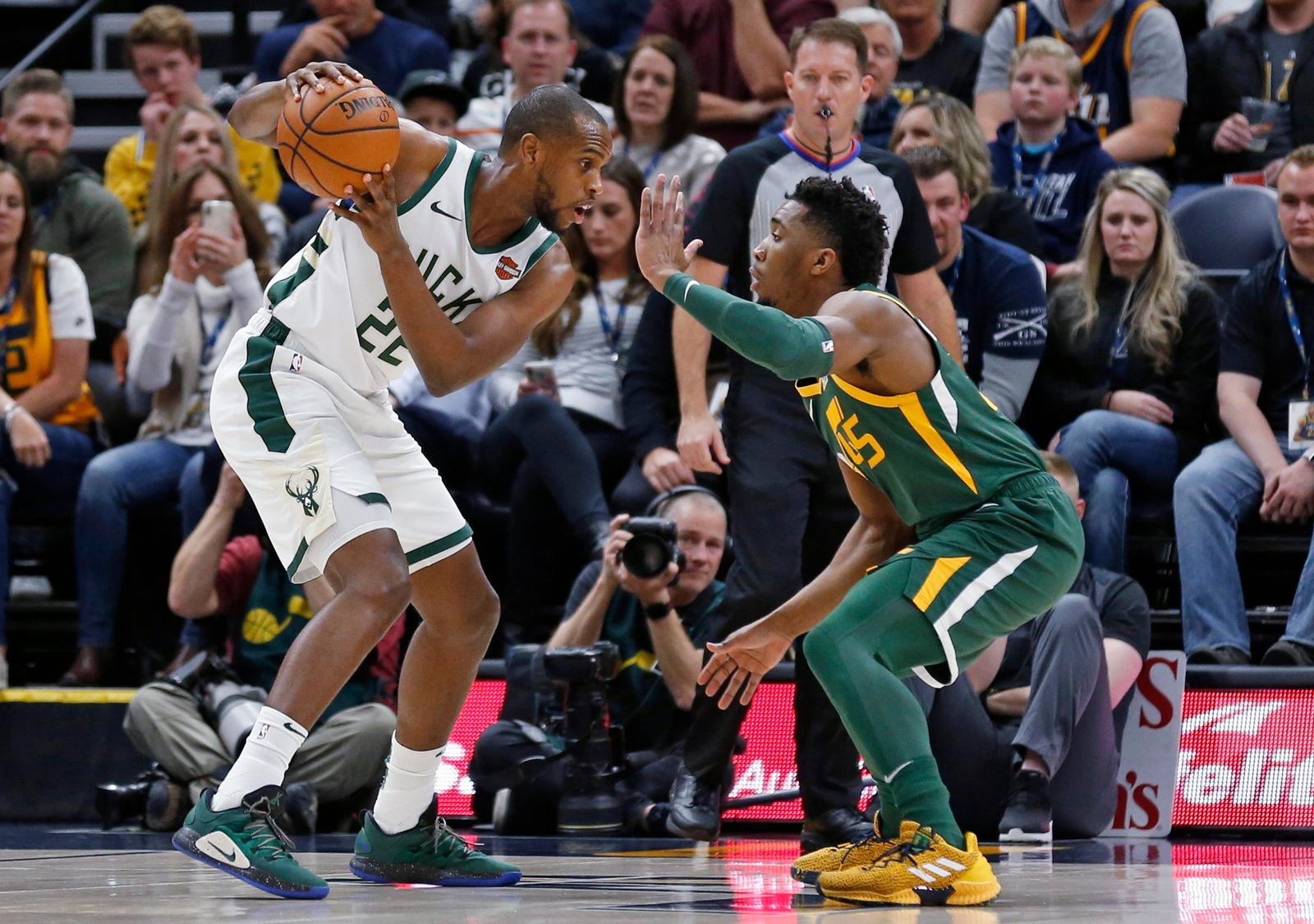 Utah Jazz guard Donovan Mitchell (45) defends against Milwaukee Bucks forward Khris Middleton (22) during the first half of an NBA basketball game Saturday, March 2, 2019, in Salt Lake City. (AP Photo/Rick Bowmer)