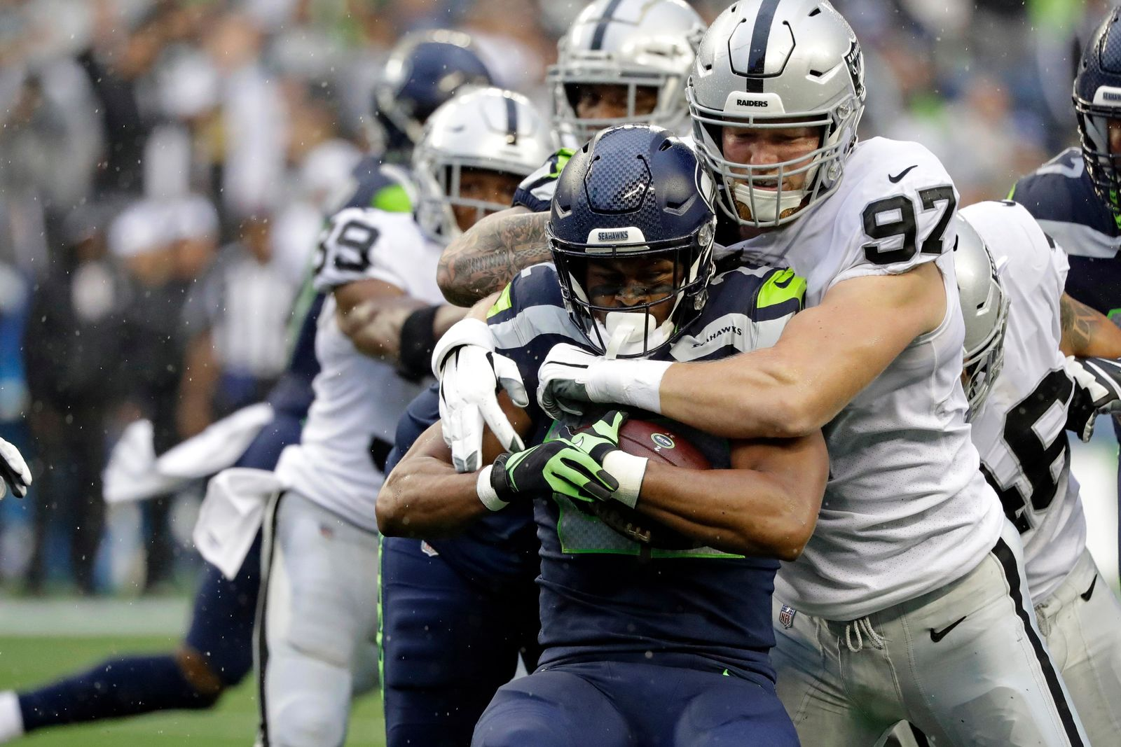 Seattle Seahawks running back C.J. Prosise, center, is tackled by Oakland Raiders defensive end Josh Mauro (97) during the first half of an NFL football preseason game Thursday, Aug. 29, 2019, in Seattle. (AP Photo/Elaine Thompson)