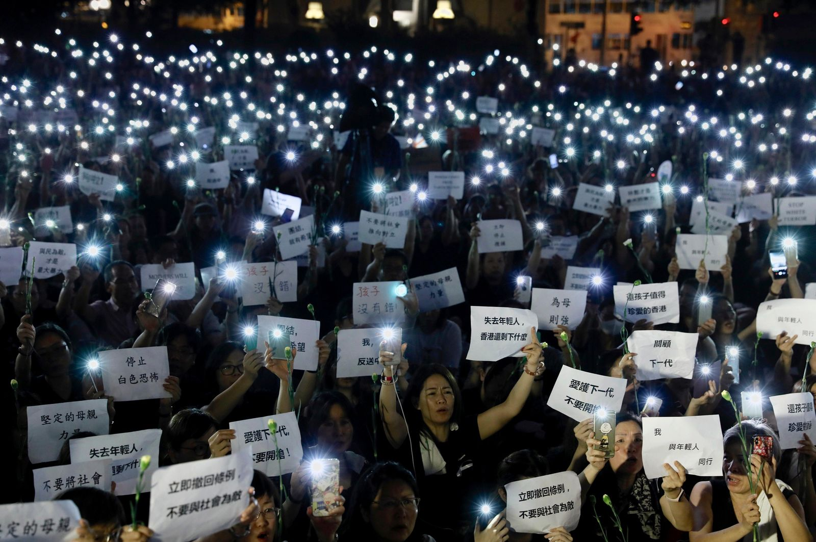 "Hundreds of mothers holding placards, some of which read ""If we lose the young generation, what's left of Hong Kong"", and lit smartphones protest against the amendments to the extradition law in Hong Kong on Friday, June 14, 2019. (AP Photo/Vincent Yu)"