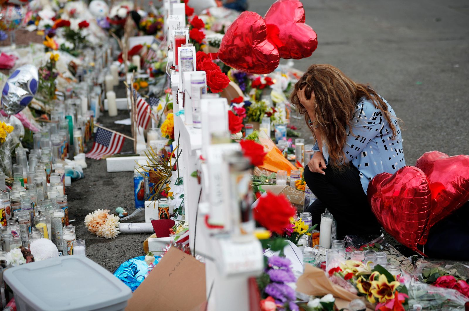 Gloria Garces kneels in front of crosses at a makeshift memorial near the scene of a mass shooting at a shopping complex Tuesday, Aug. 6, 2019, in El Paso, Texas. (AP Photo/John Locher)