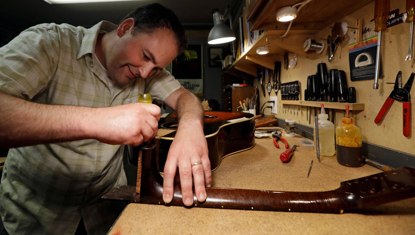 Jacob Tuel, owner of Burning River Guitars, repairs the neck on a guitar, Monday, June 10, 2019, in Akron, Ohio. Tuel named his guitar shop after the 1969 blaze on the Cuyahoga River, in Cleveland. (AP Photo/Tony Dejak)