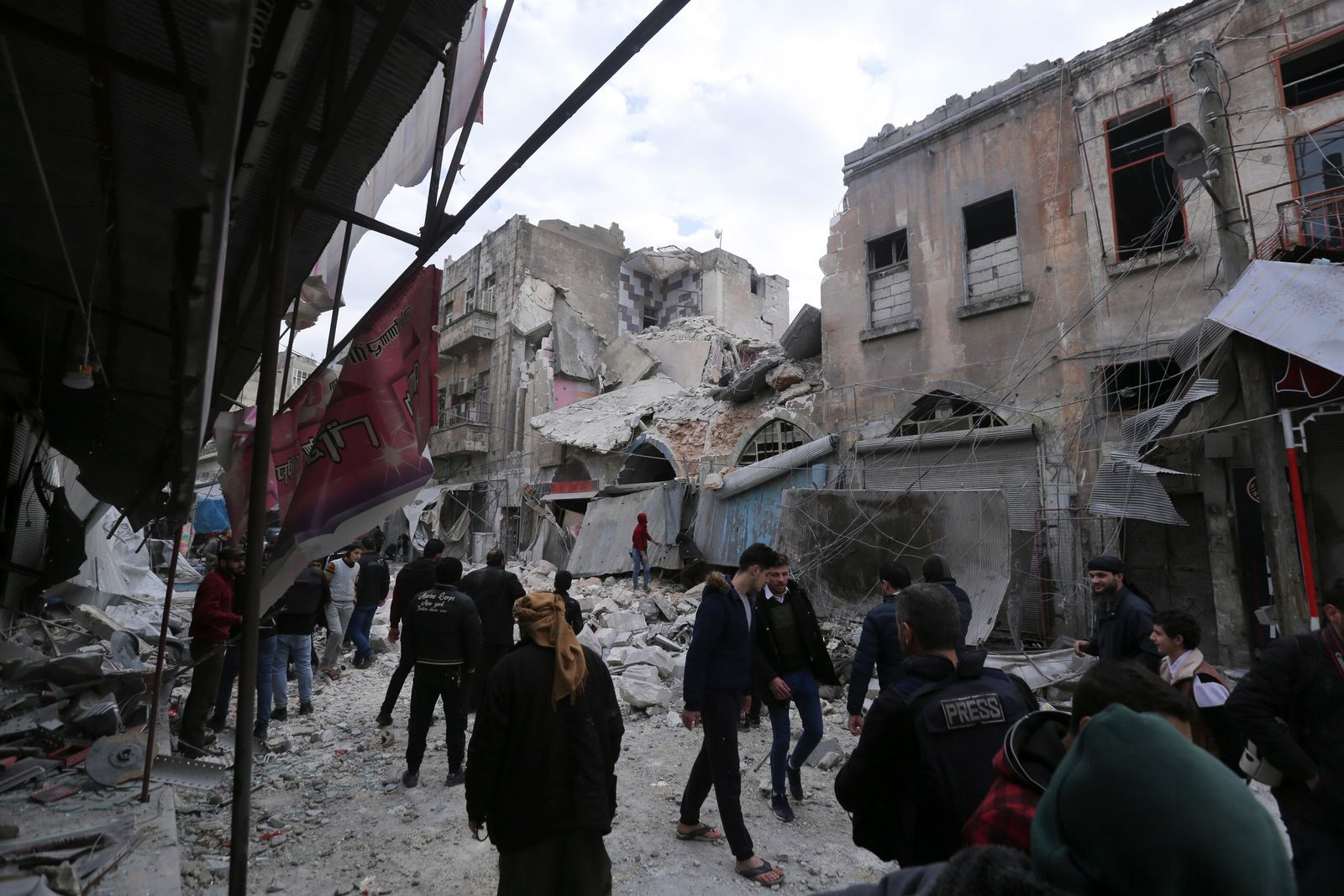 People walk past destruction by the government airstrikes in the town of Ariha, in Idlib province, Syria, Wednesday, Jan. 15, 2020. . (AP Photo/Ghaith Alsayed)
