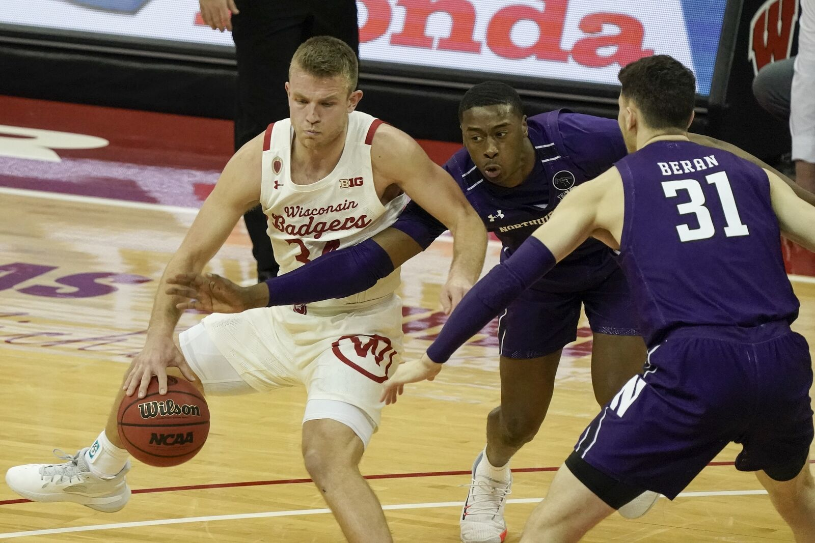 Wisconsin's Brad Davison tries to get past Northwestern's Chase Audige and Robbie Beran (31) during the second half of an NCAA college basketball game Wednesday, Jan. 20, 2021, in Madison, Wis. (AP Photo/Morry Gash)
