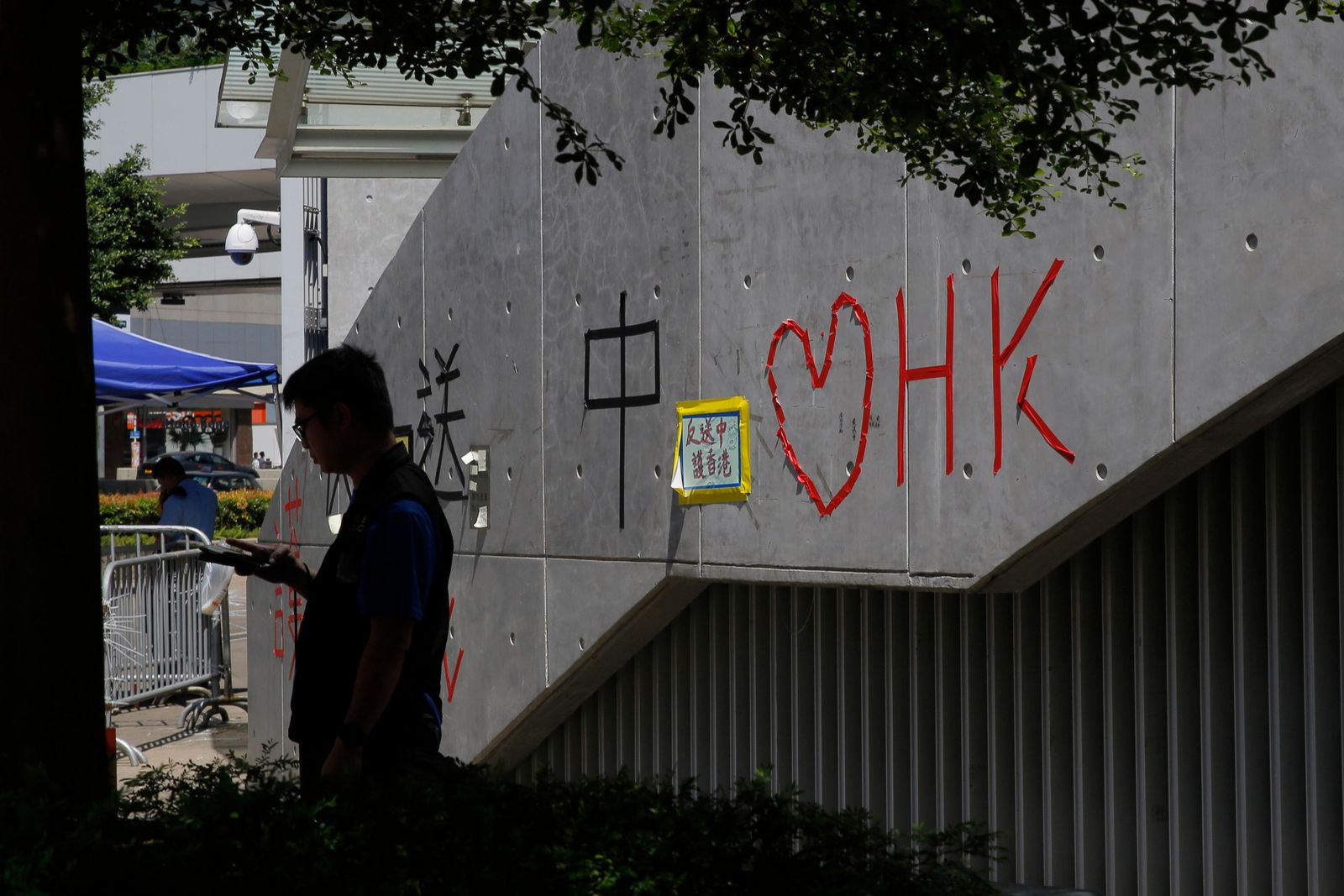 "A police officer stands next to ""Love Hong Kong"" words formed with tape near the Legislative Council, in Hong Kong, Saturday, June 15, 2019. (AP Photo/Kin Cheung)"