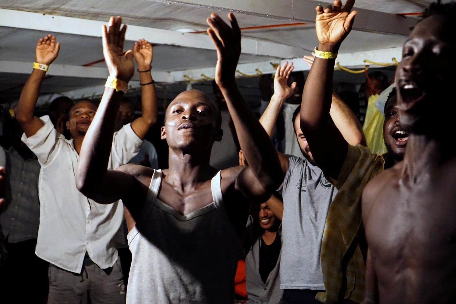 Migrants onboard the Open Arms vessel celebrate the news of an Italian prosecutor who has ordered that the migrants be disembarked on the island of Lampedusa, southern Italy, Tuesday, Aug. 20, 2019. (AP Photo/Francisco Gentico)