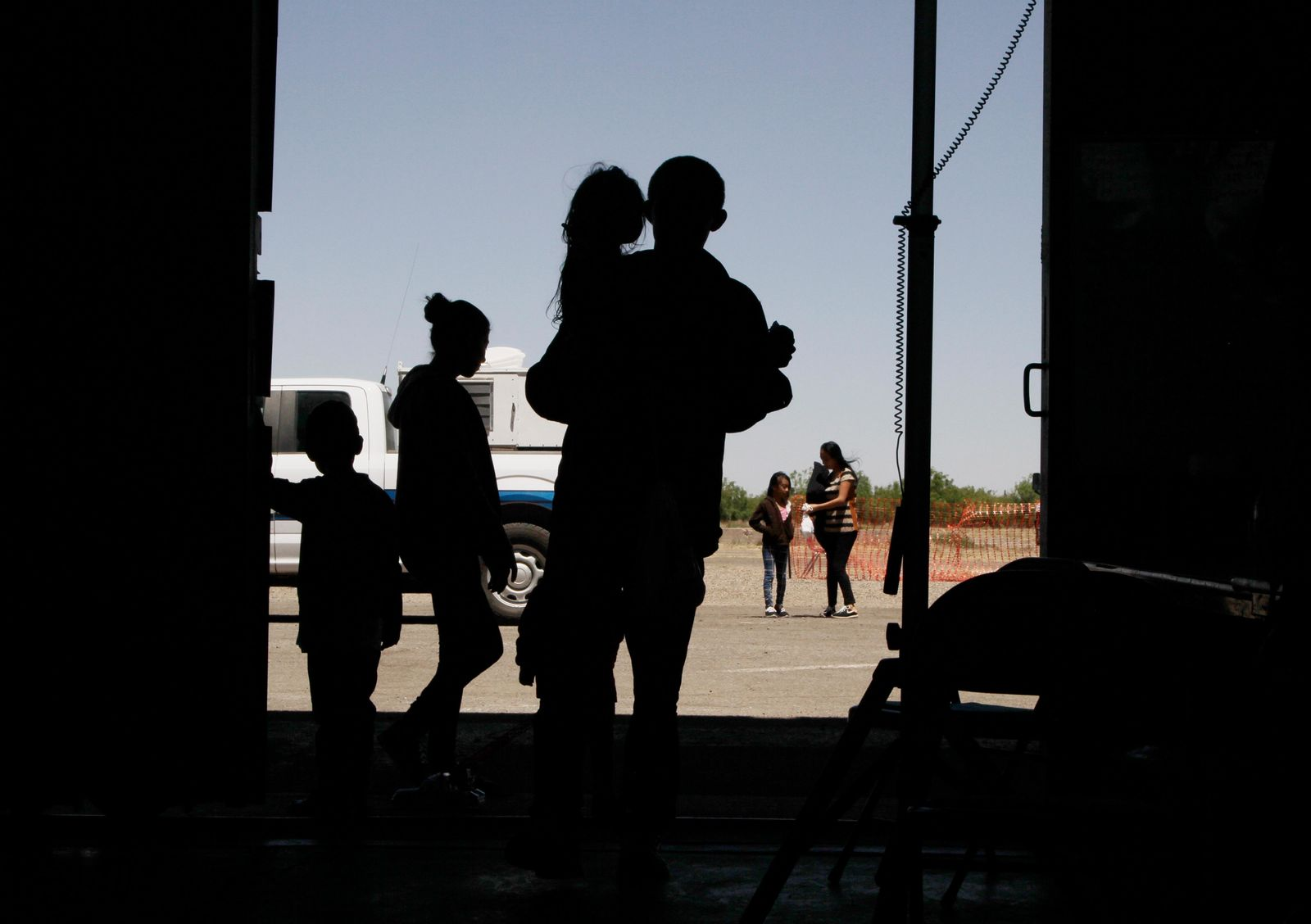 In this Wednesday, May 22, 2019, migrants mainly from Central America guide their children through the entrance of a World War II-era bomber hanger in Deming, N.M.{ } (AP Photo/Cedar Attanasio)