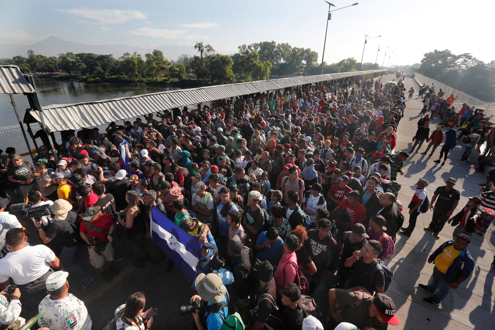Migrants line up behind an Honduran flag at the border crossing between Guatemala and Mexico in Tecun Uman, Guatemala, Saturday, Jan. 18, 2020. More than a thousand Central American migrants surged onto a bridge spanning the Suchiate River between that marks the border between both countries as Mexican National Guardsmen attempted to impede their journey north. (AP Photo/Marco Ugarte)
