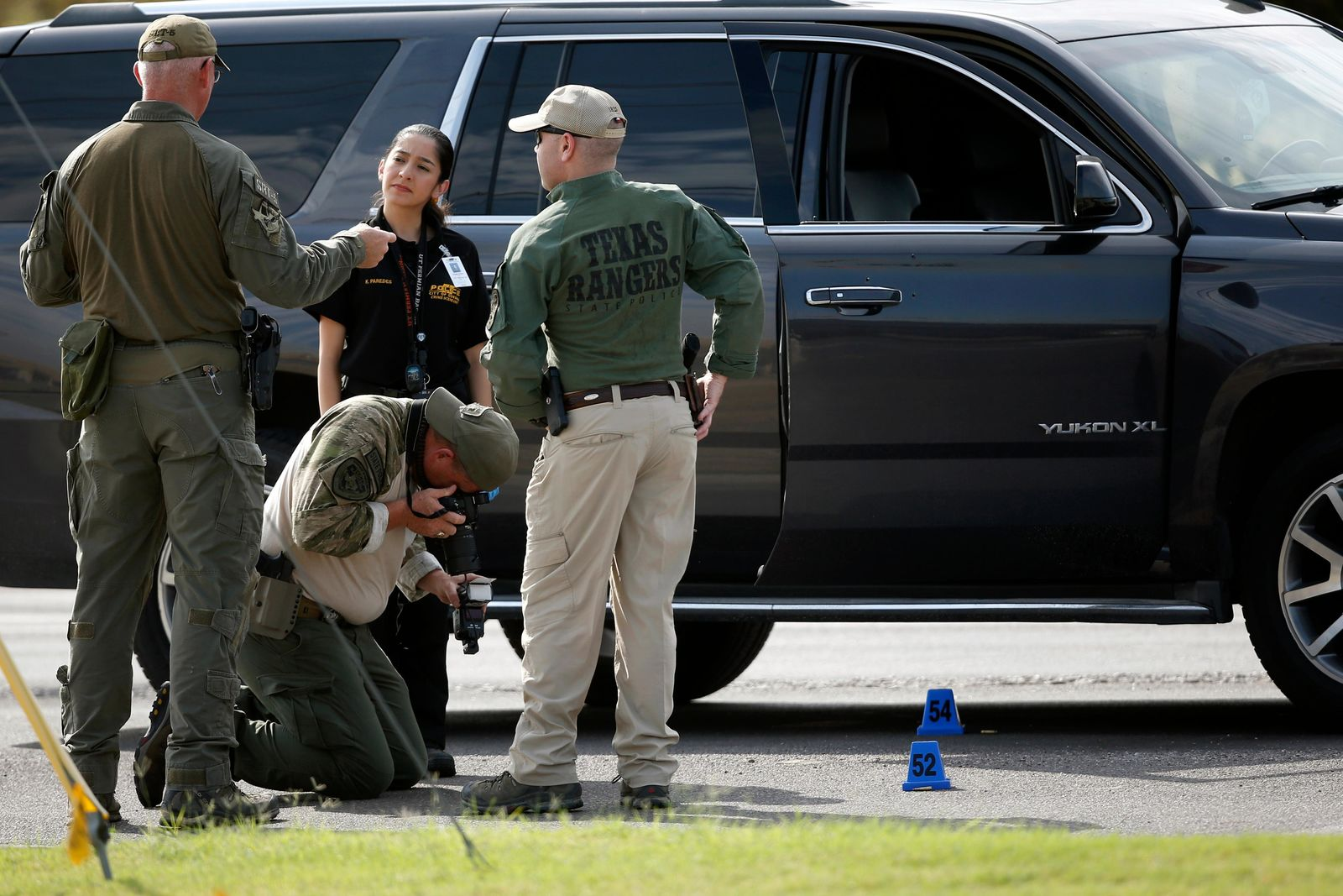 Law enforcement officials process a scene involved in Saturday's shooting, Sunday, Sept. 1, 2019, in Odessa, Texas. The death toll in the West Texas shooting rampage increased  Sunday as authorities investigated why a man stopped by state troopers for failing to signal a left turn opened fire on them and fled, shooting more than a dozen people as he drove before being killed by officers outside a movie theater.  (AP Photo/Sue Ogrocki)