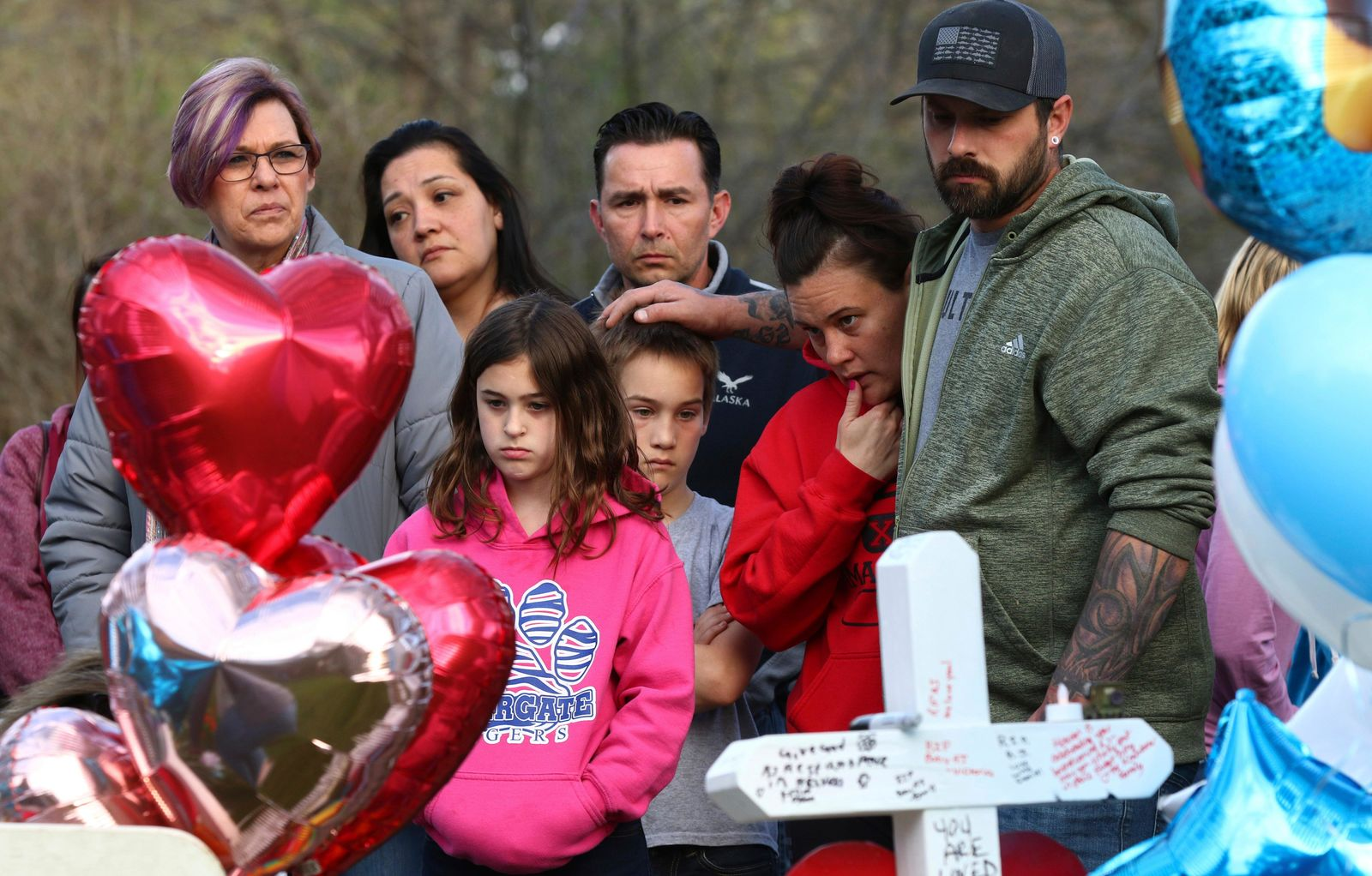 "Mourners view a growing memorial outside the home of 5-year-old Andrew ""AJ"" Freund Wednesday, April 24, 2019, in Crystal Lake, Ill. Andrew's body was found in a wooded area in Woodstock Wednesday, and the boy's parents have been charged with his murder. (John J. Kim/Chicago Tribune via AP)"