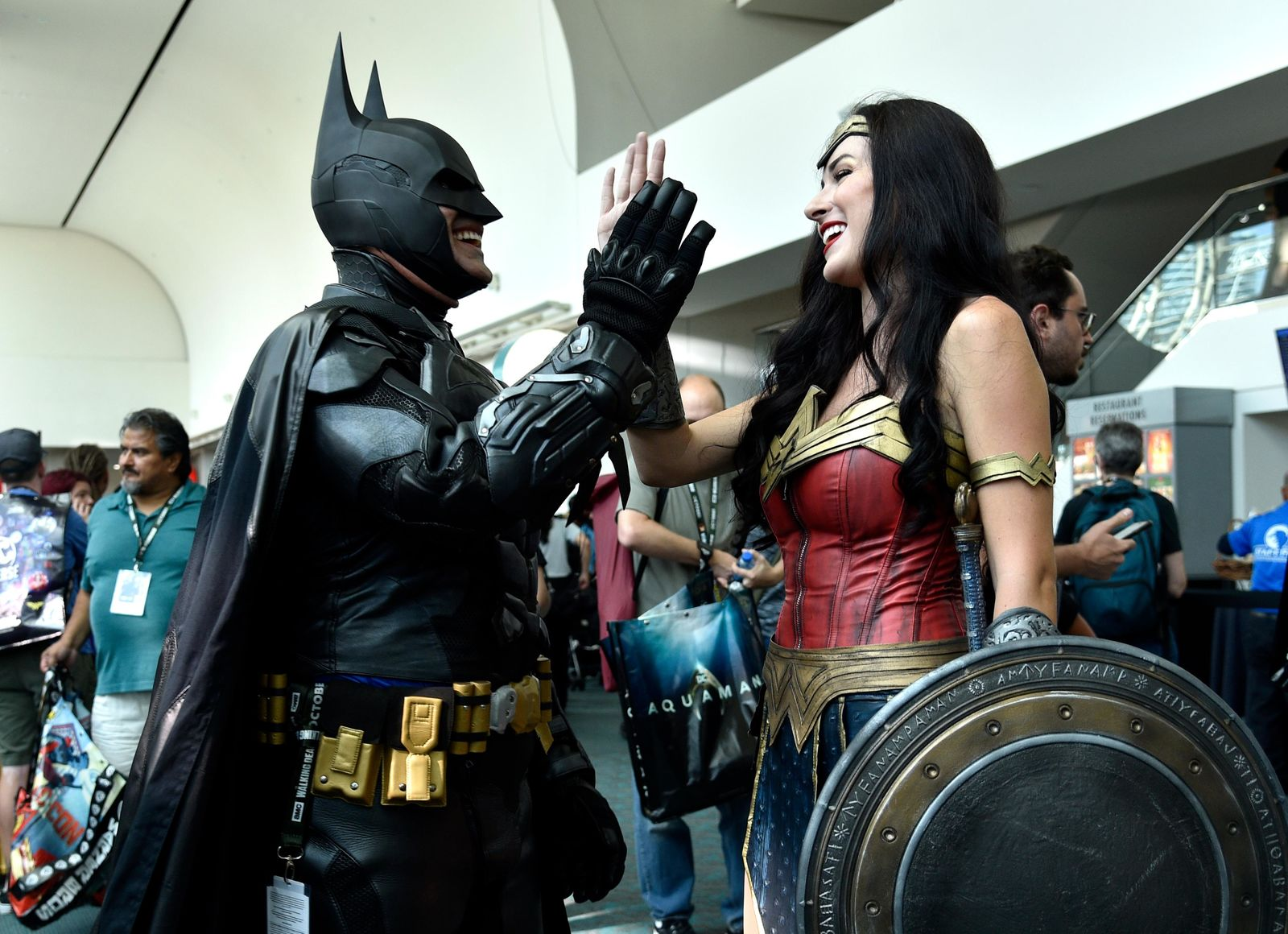 Armando Abarca, left, dressed as Batman, and Jessica Rose Davis, dressed as Wonder Woman, of Los Angeles, high five each other as they attend day one of Comic-Con International on Thursday, July 19, 2018, in San Diego.(Photo by Chris Pizzello/Invision/AP)