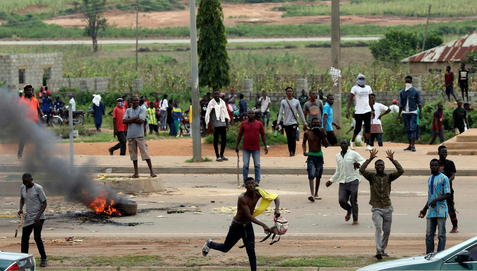 Protesters throw rocks at policemen during an attack on South African business, in Abuja, Nigeria, Wednesday Sept. 4, 2019.{ } (AP Photo)