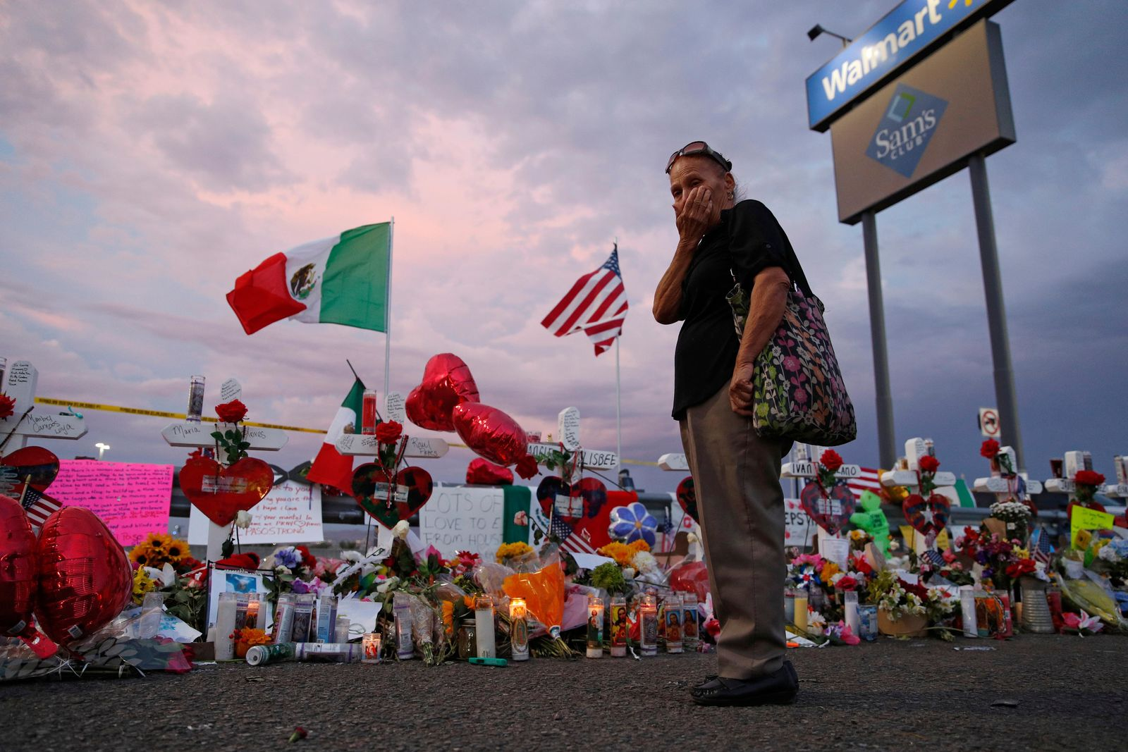 Catalina Saenz wipes tears from her face as she visits a makeshift memorial near the scene of a mass shooting at a shopping complex Tuesday, Aug. 6, 2019, in El Paso, Texas. (AP Photo/John Locher)